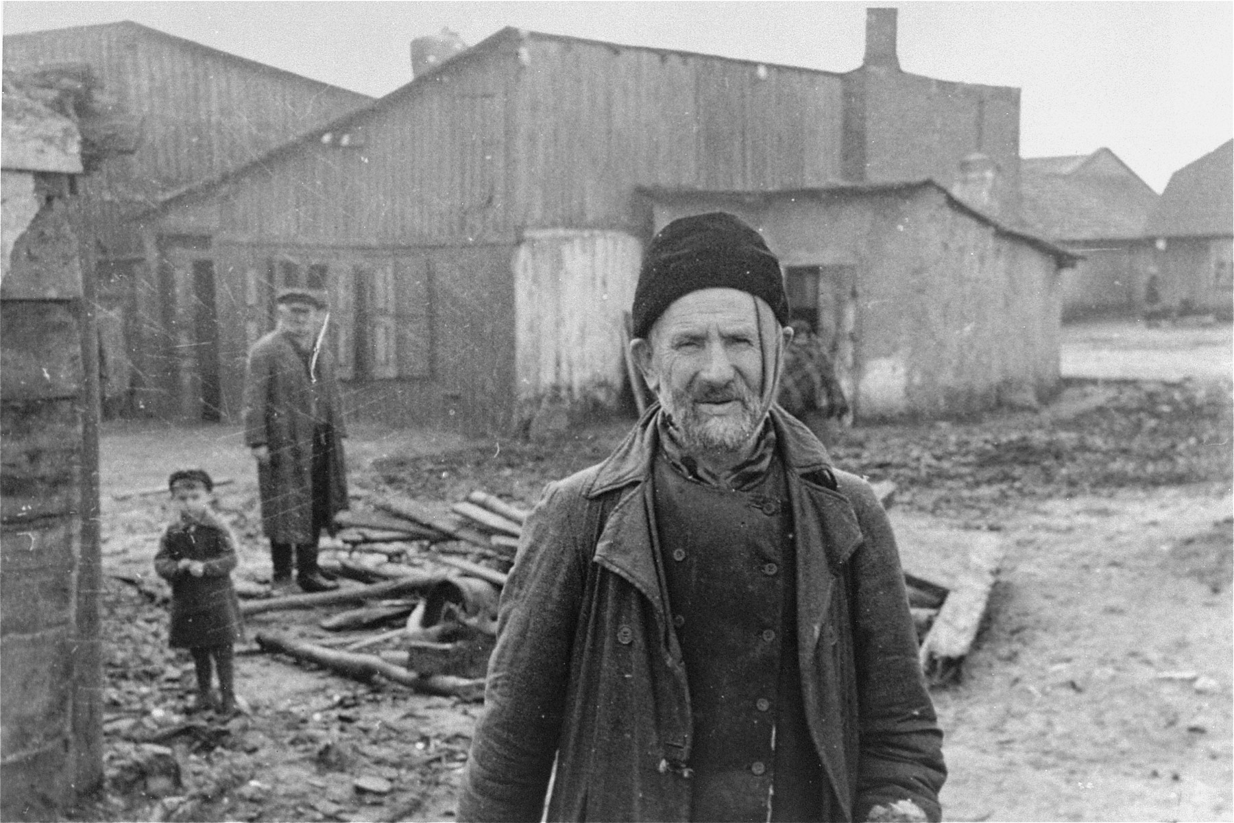 An elderly Jew stands in an open area between buildings in the Kovno ghetto, in front of a pile of wood.