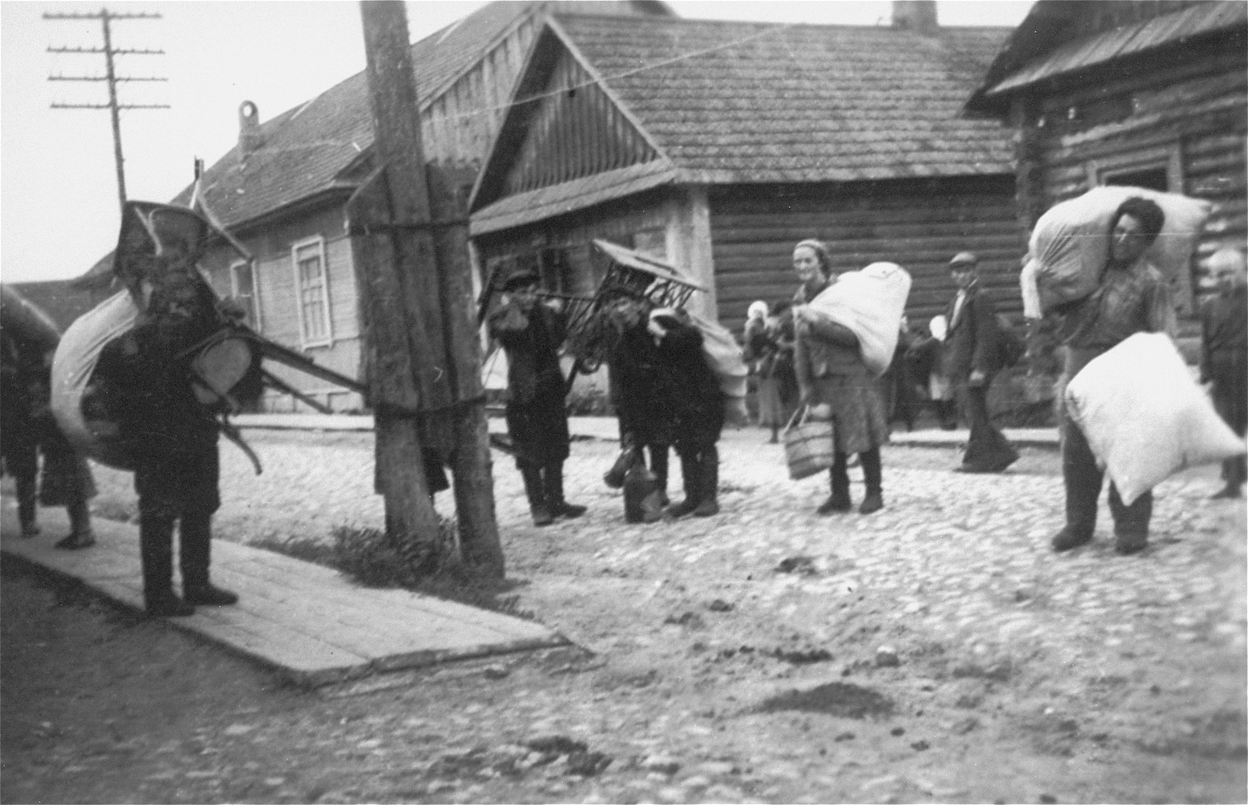 Jews in the Kovno ghetto carry furniture and large bundles.  They are probably moving to new homes following a reduction of the ghetto's borders.