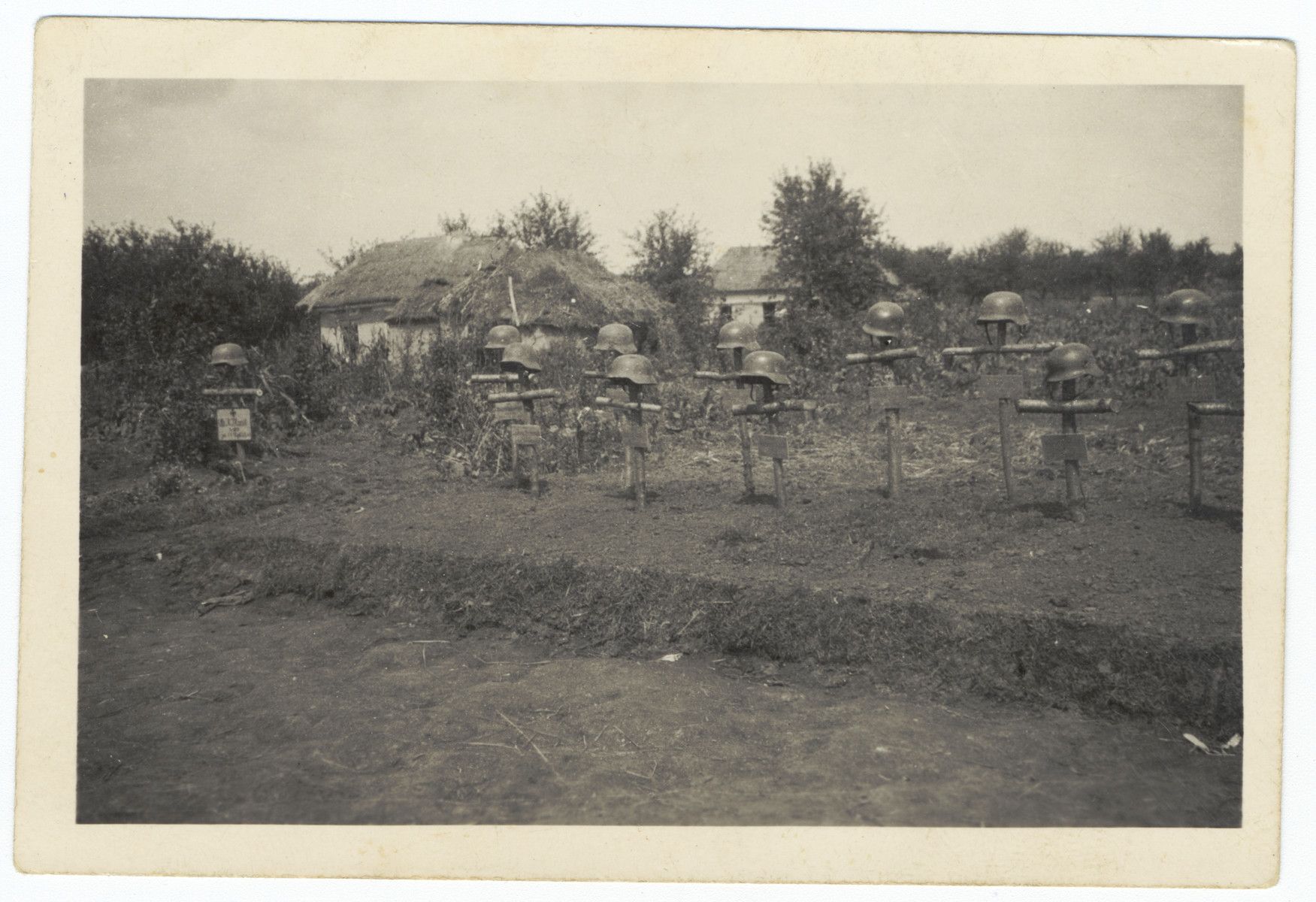 View of a make-shift German military cemetery consisting of crude crosses and helmets.