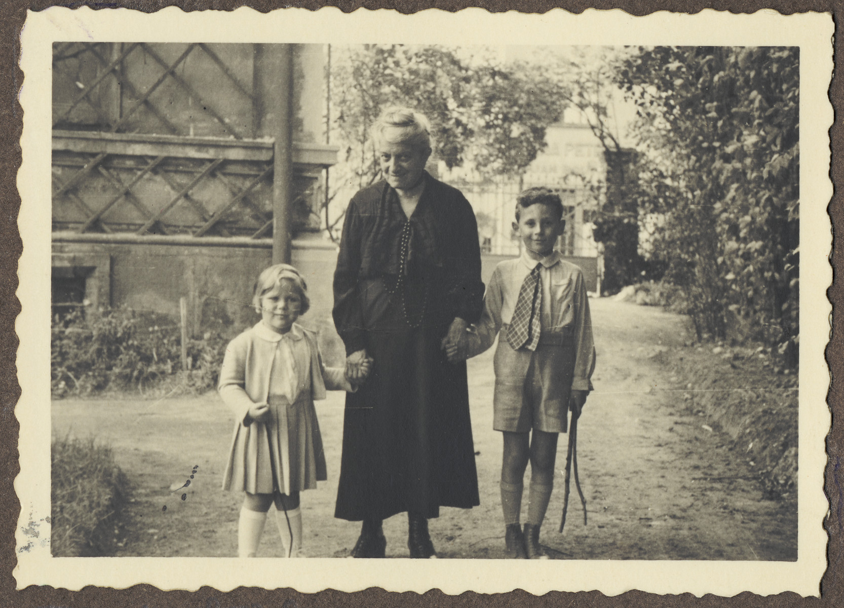 An elderly Czech Jewish woman walks through a garden with two young relatives.  Pictured on the right is Michal Kraus; on the left is his cousin Eva Schur.  The woman in the center is probably Eva's great grandmother.  Eva Schur, was the daughter of Franta Schur, the cousin of Michal Kraus.  Eva perished in Auschwitz with her mother and brother, while her father, Franta Schur survived the war in England.  The picture was taken in the garden of the house belonging to her grandmother, Jenny Schur.