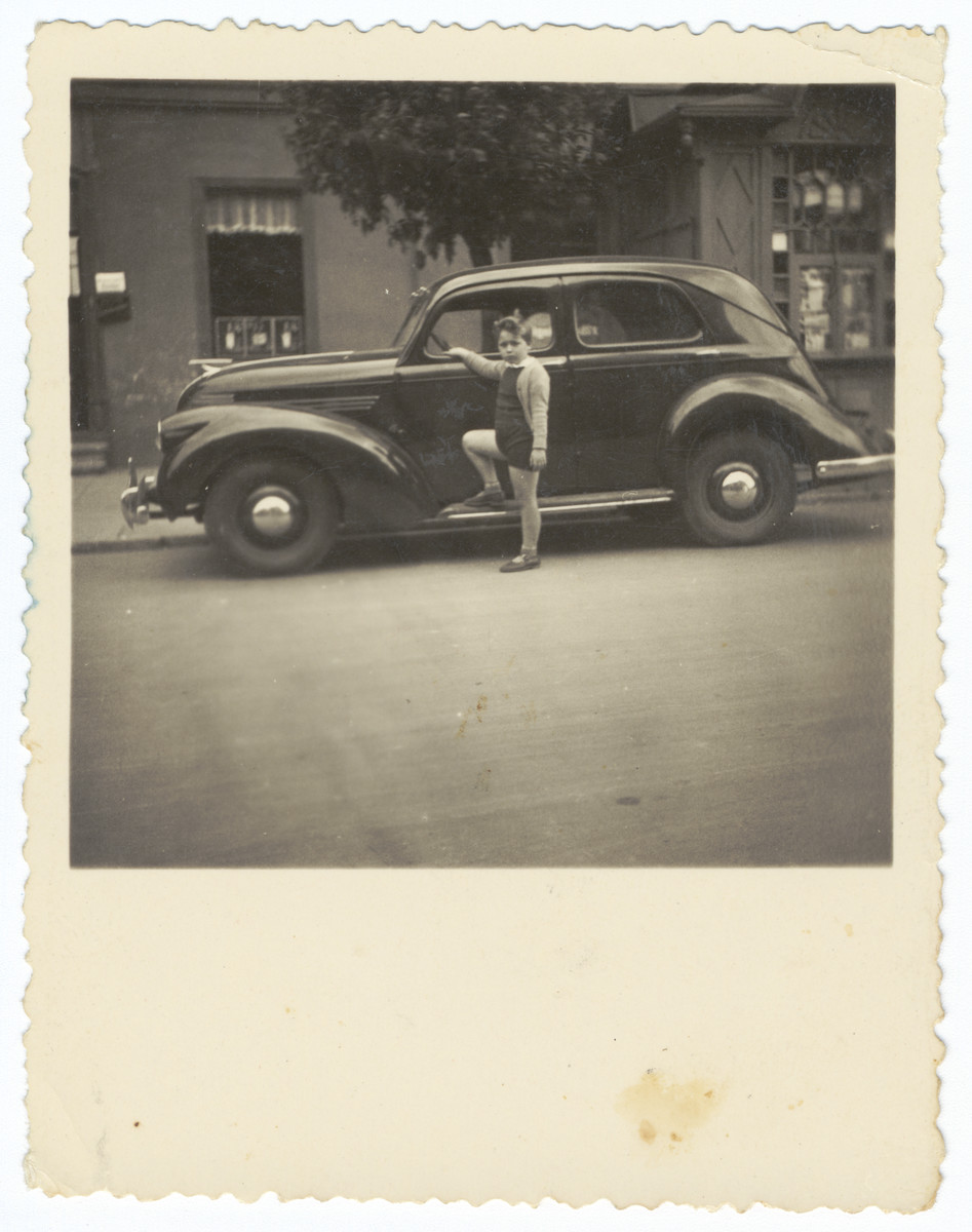 Simon Frumkin stands next to his parent's automobile, a 1938 Willys-Overland in downtown Kaunas.