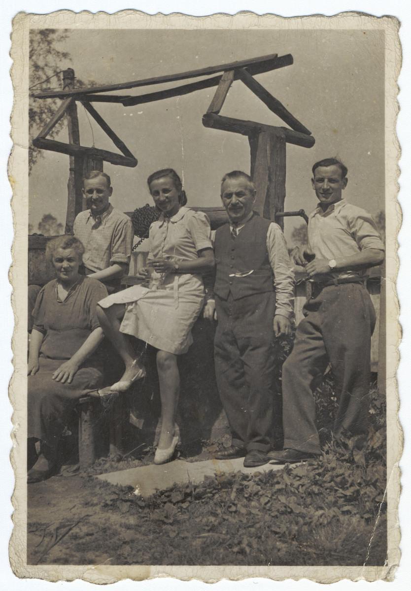 Group portrait of a Polish Jewish family.  Rudolf Hoffman is pictured standing on the far left next to his wife, Regina Polland Hoffman. The man on the far right, holding a glass of wine, is Adolf (Dolek) Polland, the brother of Regina.