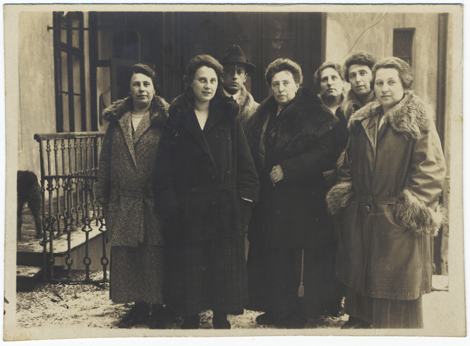 A Czech-Jewish woman poses surrounded by her six grown children outside her home in Nachod.  Mathilde Goldschmid is in the center.  Her children from left to right are Jenny (b.1878), Lola (b.1898), Hans (b.1891), Alice (b.1880), Lily (b.1884) and Marianna (b. 1886).  All five daughters perished in the Holocaust.  Only Hans survived the war in Palestine.