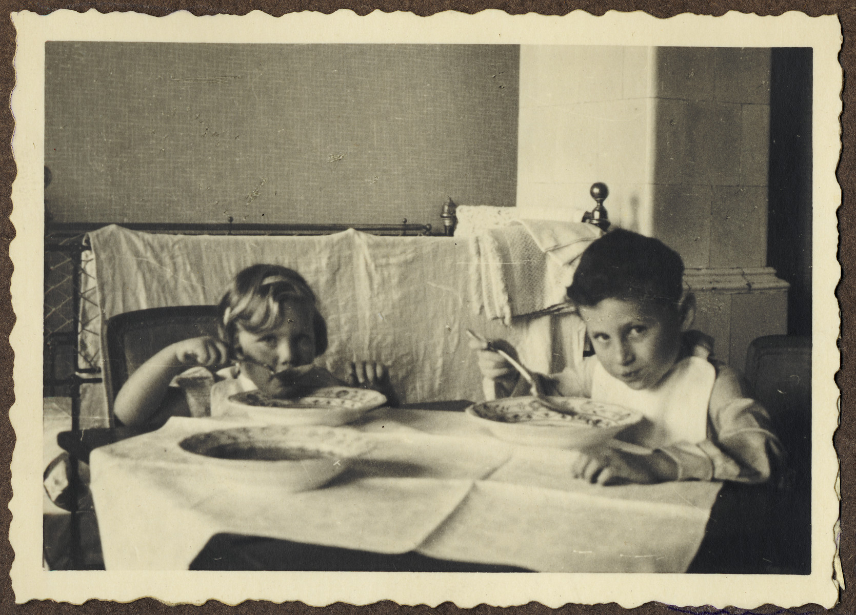 Two young children sit at a table and eat soup.  Pictured on the right is Michal Kraus.  On the left is Eva Schur, the daughter of his cousin.    Eva's grandmother, Jenny Schur nee Goldschmid, was the sister of Michal's mother.  Eva was the daughter of Franta Schur, the cousin of Michal Kraus.  Eva perished in Auschwitz with her mother and brother, while her father, Franta Schur survived the war in England.  The picture was taken in the home of her grandmother, Jenny Schur.