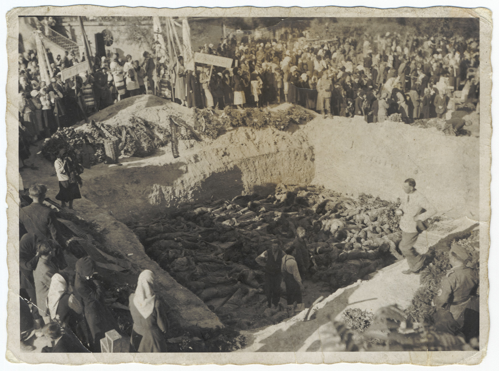 Civilians gather by a mass grave [probably during the invasion of the Soviet Union.]