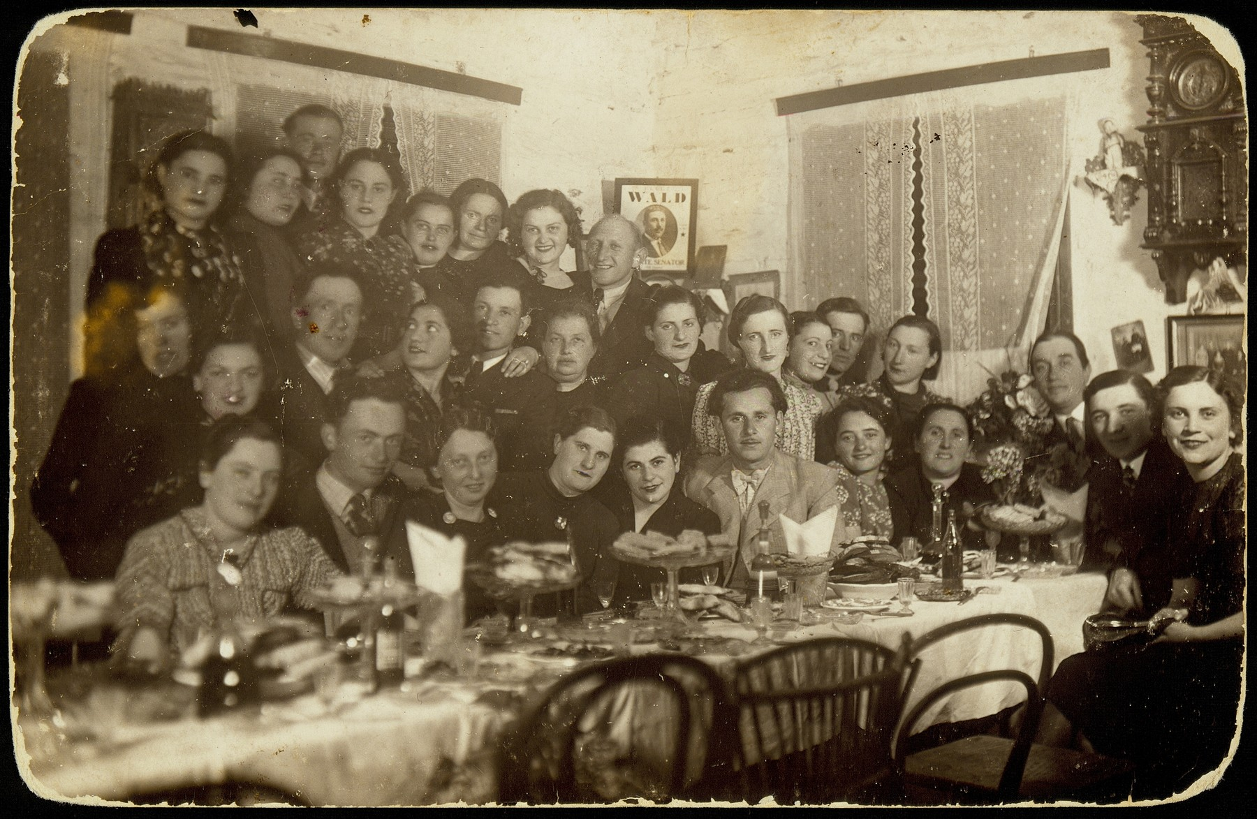 Going-away party in honor of a young woman's imminent departure for Palestine.    Top row at far right, Yehiel Blacharowicz.  Middle row at far right, Szeine Blacharowicz and fourth from right is Miriam Kabacznik Shulman.  Sitting fifth from right is Kreinele Kanichowski, sixth from right, Zvi Hirshke Schwartz and third from left is Shoshana Katz.   Miriam Kabacznik Shulman  and Szeine Blacharowicz survived the Holocaust is hiding.  Kreinele Kanichowski was murdered by soldiers of the Polish Home Army.  Most of the people in the photo were murdered by the Germans during the September 1941 mass killing action in Eisiskes and in other locations.