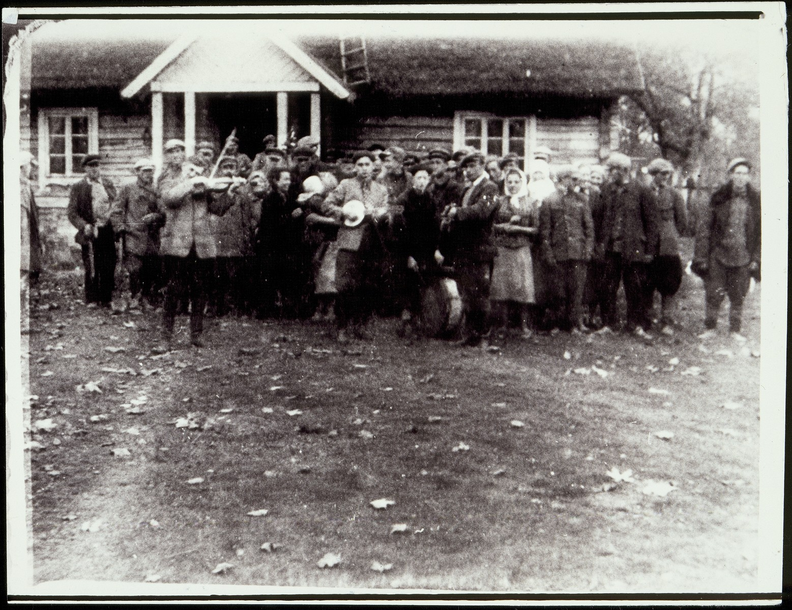 Peasants, some with musical instruments, celebrate the redistribution of land in the region.    Luba Ginunski, one of the shtetl's leading Communists, distributed land to five hundred poor Polish peasants in the autumn of 1940.  Luba, is pictured dressed in black, speaking to a woman with a white kerchief.  She survived the war in the Soviet interior and afterwards immigrated to Israel.