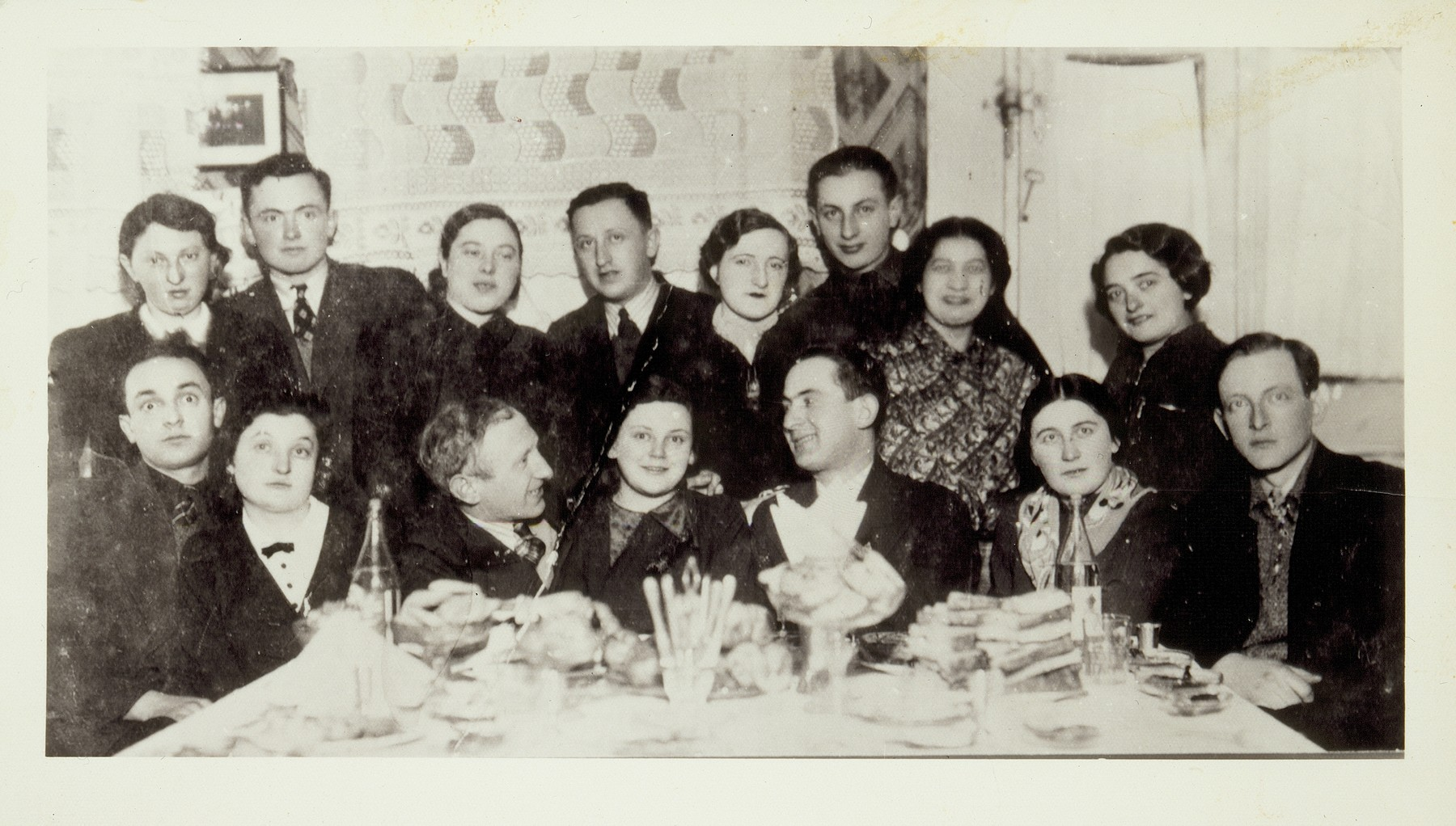 Group portrait of Jewish couples at a Saturday night party in Eisiskes.   Among those pictured are Shepshke (Shabtai) Sonenson (bottom right), Yehiel Blacharowicz (seated third from the left), Krienele Kanichowski (standing at the right), Miriam Kabacznik (standing fourth from the right) and Shoshana Katz (standing at the left).  Miriam Kabacznik survived the war in hiding; Krienele Kanichowski was killed by a Pole.  All the others died in killing actions in Eisiskes and nearby towns.