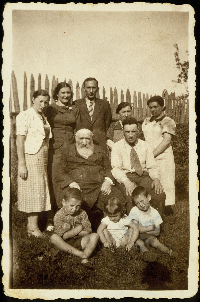 Reb Reuven Kaganov sits in his yard surrounded by his children and grandchildren.    Standing from right to left: Ida Kanichowski Kaganov, Fruml Blacharowicz, Szymen Kaganov and his wife Judith (Yonah), and Szeina Blacharowicz.  Sitting from right to left: Leibke Kaganov, and Reb Reuven  Kaganov. Children sitting on the ground from right to left: Motele, Shifrale and Yaakov Kaganov.    Reuven  Kaganov died a natural death. Szymen Kaganov immigrated to Palestine with his wife and son Yaakov, who later moved to America and contributed new inventions for Kodak before being killed in a car accident.  Ida Kaganov and her two children, Motele and Shifrale, were murdered by Poles.  Fruml Blacharowicz was murdered by members of the Polish Home Army on March 19, 1944. Leibke Kaganov was murdered in the September 1941 massacre.  Szeina Blacharowicz survived the Holocaust hiding in a forest.
