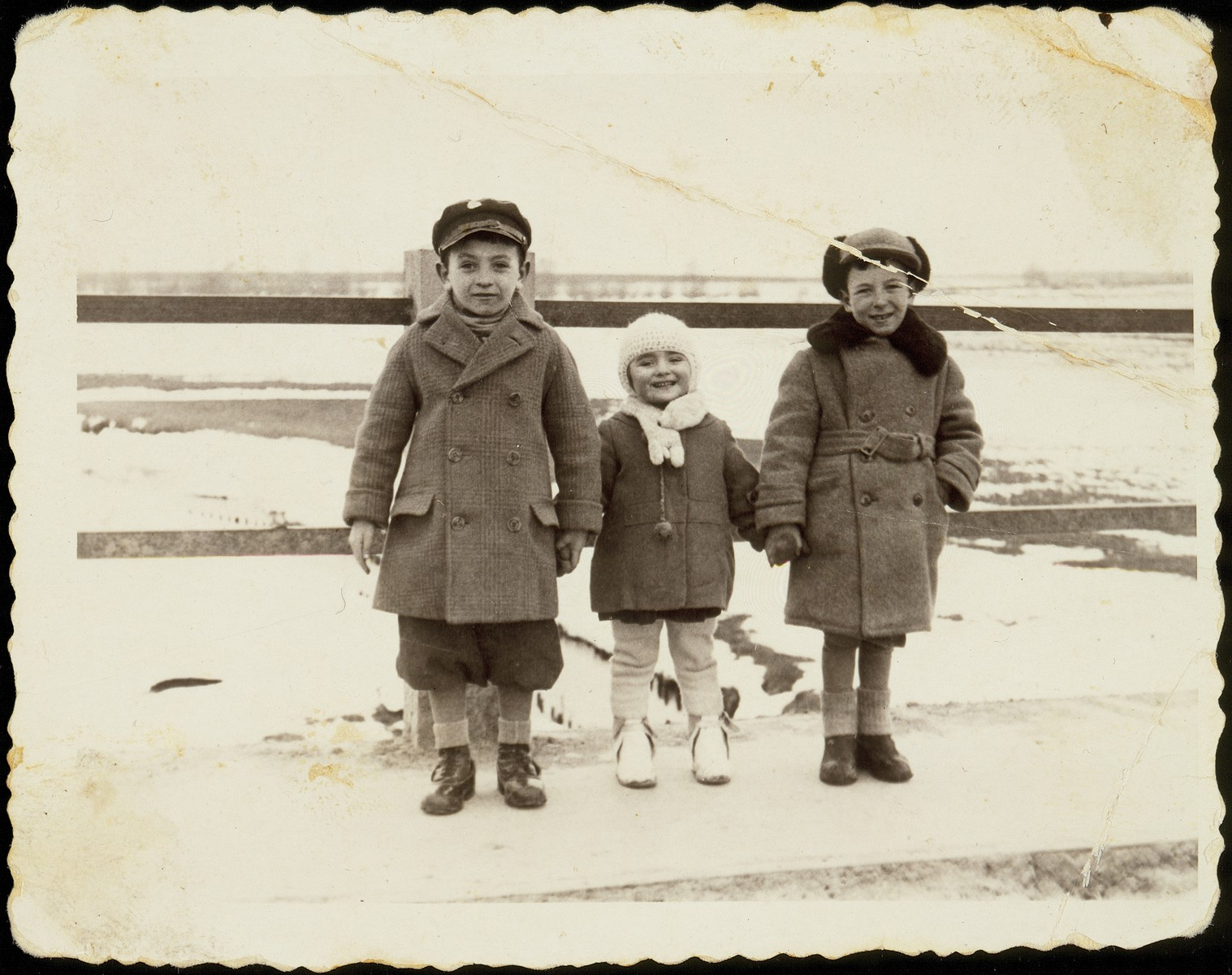 Three young cousins stand on a snowy bridge in Eisiskes.    (Right to Left:): Yankele with his two cousins, Shifrale and her brother Motele, the children of Ida and Shimon Kaganov. Shifrale and Motele were murdered by soldiers of the Polish Home Army. Yankele was killed in a car accident in the United States.
