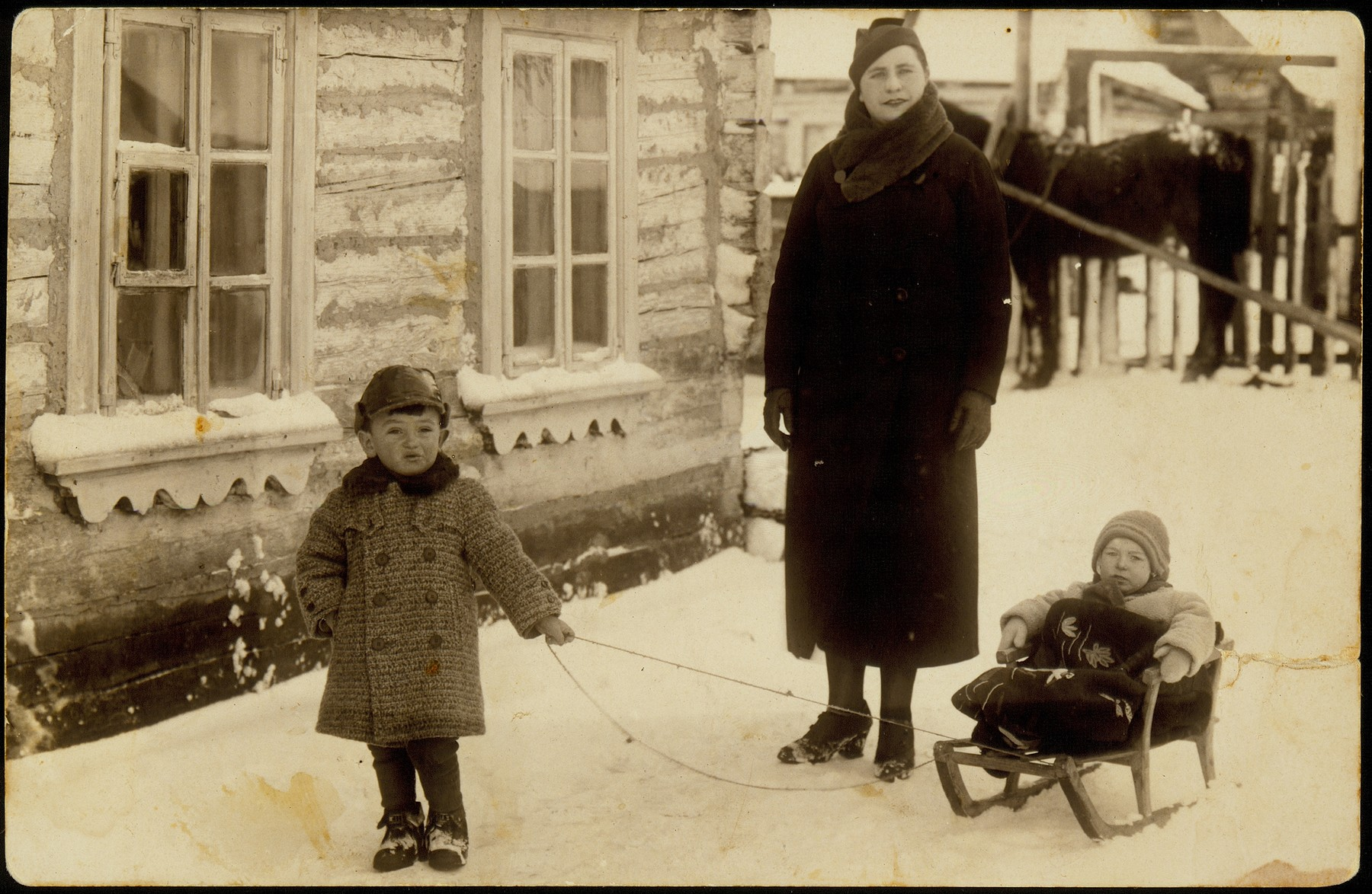 Two young Jewish cousins play in the snow in Eisiskes.  Pictured is Mtele Kaganov pulling his cousin, Yankele Kaganov on a sled in the backyard of the home of Shaina Blacharowicz.  An adult relative supervises the two children.
