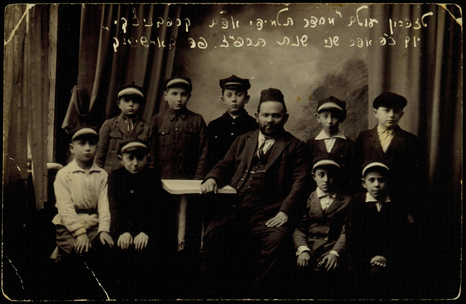 Religious school (cheder) students in Eisiskes.    Seated in the center is the teacher, Eliezer David Mordekhai Krapovnitski, who was known as Reb Adam.  The Heder boys are (standing, right to left)  Shlomo Pilushki, Moshe Dovid Katz, Shmuel Shlanski, Avraham Kabacznik, and Shlomo Dugaczanski; (seated) Sander Nochomowicz, Alexander Zisl Hinski, Yehiel Blacharowicz, and a boy known as Hishveh  from the village of Golmecziszki.   Shmuel and Hishveh immigrated to America, Sander to Argentina, Zisl to Palestine.  Of the others, Avraham died a natural death; the rest were murdered by the Germans during the September 1941 killing action in Eisiskes.