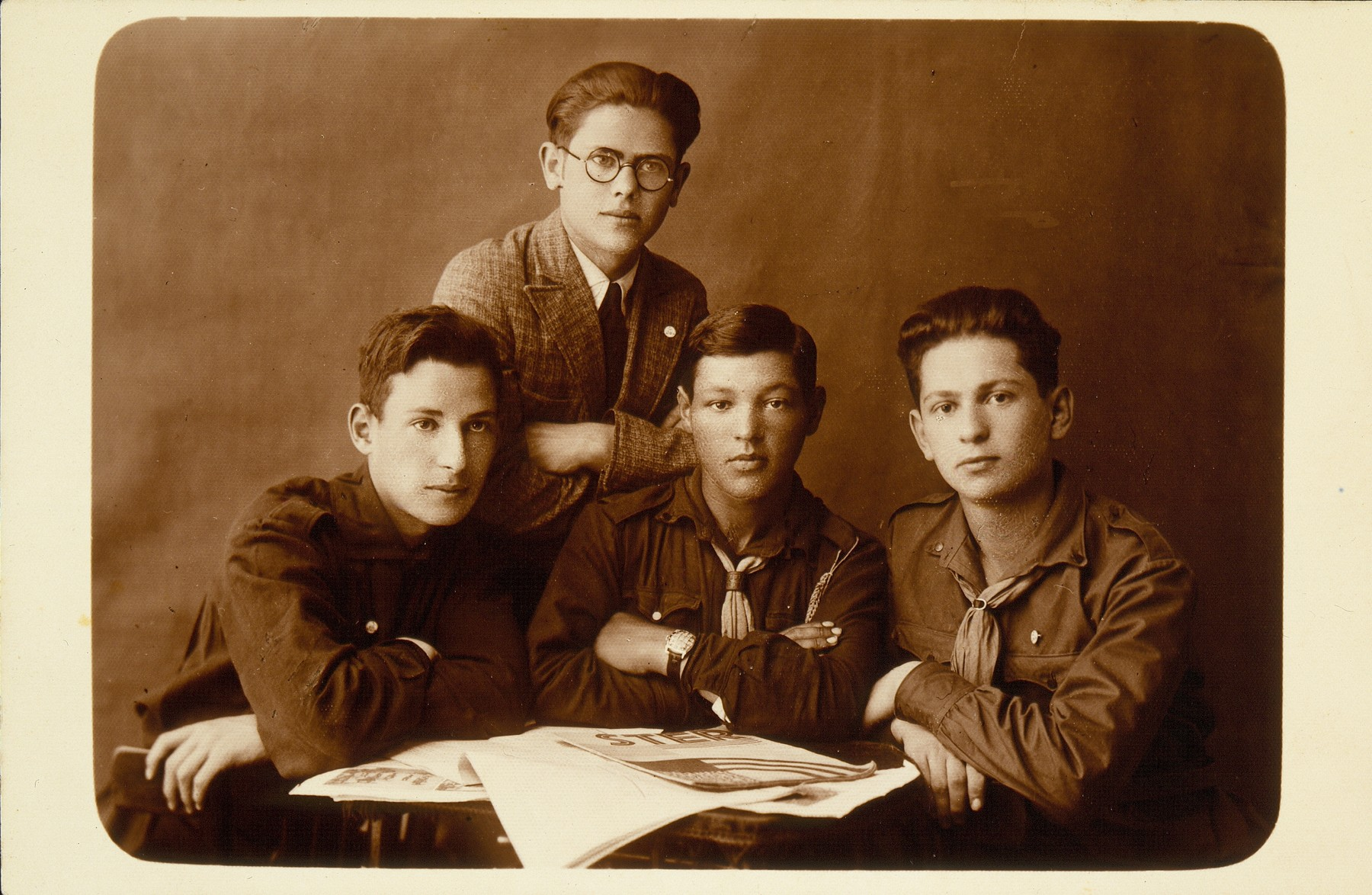 Four young members of the Betar youth movement gather around a table strewn with newspapers.   Faivl Glombocki (sitting in center), on his right is Dov Wilenski, on his left Hanan Polaczek, and a friend  (standing) from Chiznistock, Vilna. Dov immigrated to Palestine.  Faivl came to Argentina in 1930 with his family and later immigrated to Israel.