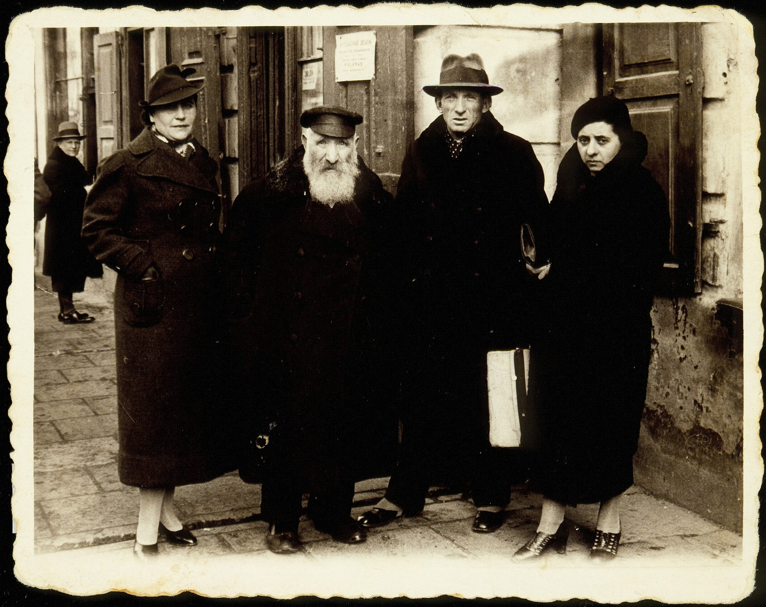 Members of the Kaganov family pose on a sidewalk in Grodno.    From right to left Judith (Yonah) Szyszenski Kaganov, her husband Szymen Kaganov, Reb Reuven Kaganov and Ida Kanichowski Kaganov.  Reb Reuven Kaganov died a natural death.  Ida Kaganov was murdered by Poles and her two children.  Szymen Kaganov and his wife Judith (Yonah), and son Yaakov immigrated to Palestine.