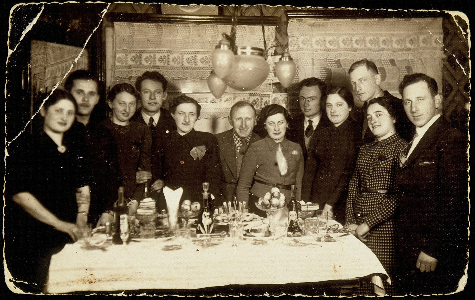 Young people enjoy a Saturday night get-together at the house of Sorl Kabacznik.  From right to left: Meir Shimon Politacki, Kreinele Kanichowski, Shepske Kabacznik, Dina Weidenberg, Leiba Levin, Frumele Abelov, Yehiel Blacharowicz, Miriam Kabacznik Shulman, Aryeh Koplevitz, Shoshana Katz, Zvi Hirshke Schwartz and Hayya Radunski.    Kreinele Kanichowski was murdered by the Polish Home Army.  Leiba Levin survived the Holocaust as a partisan.  Miriam Kabacznik Shulman survived the Holocaust in hiding. Aryeh Koplevitz immigrated to Palestine.  All the other people in the photo were murdered by the Germans in the September 1941 mass killing action.