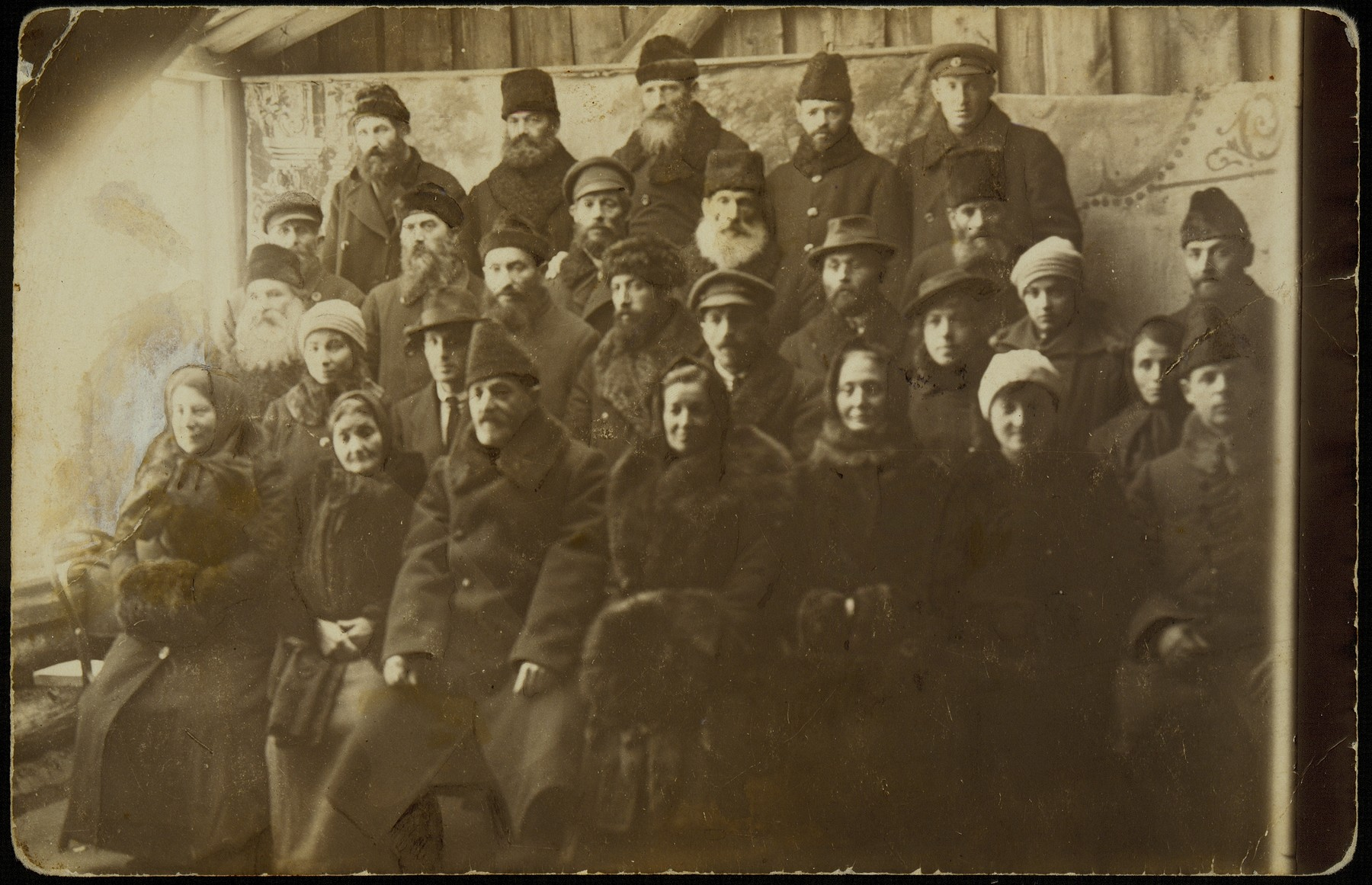 The Assistance Committee responsible for distributing  donations of money from America.   The photo was taken in honor of Aaron-Don Becker (front row, third from left), who in 1920 brought a large donation to the shtetl from the Eishyshker Society in New York.  Seated to the right of Aaron-Don is his relative Sarah Kaganowicz, to his left is Hayya Sonenson, head of the Froyen Farain (Union of Women); Libe-Gittel Rudzin; her daughter, Miriam Kaganowicz; and husband Shael, relatives of Aaron-Dan.  Among others in the photo are members of the Pachianko family, members of the Kahal, and clergy.  Standing in the back, between Aaron-Don and Hayya Sonenson, is Reb Hertz Mendl Hutner, the shtetl judge.
