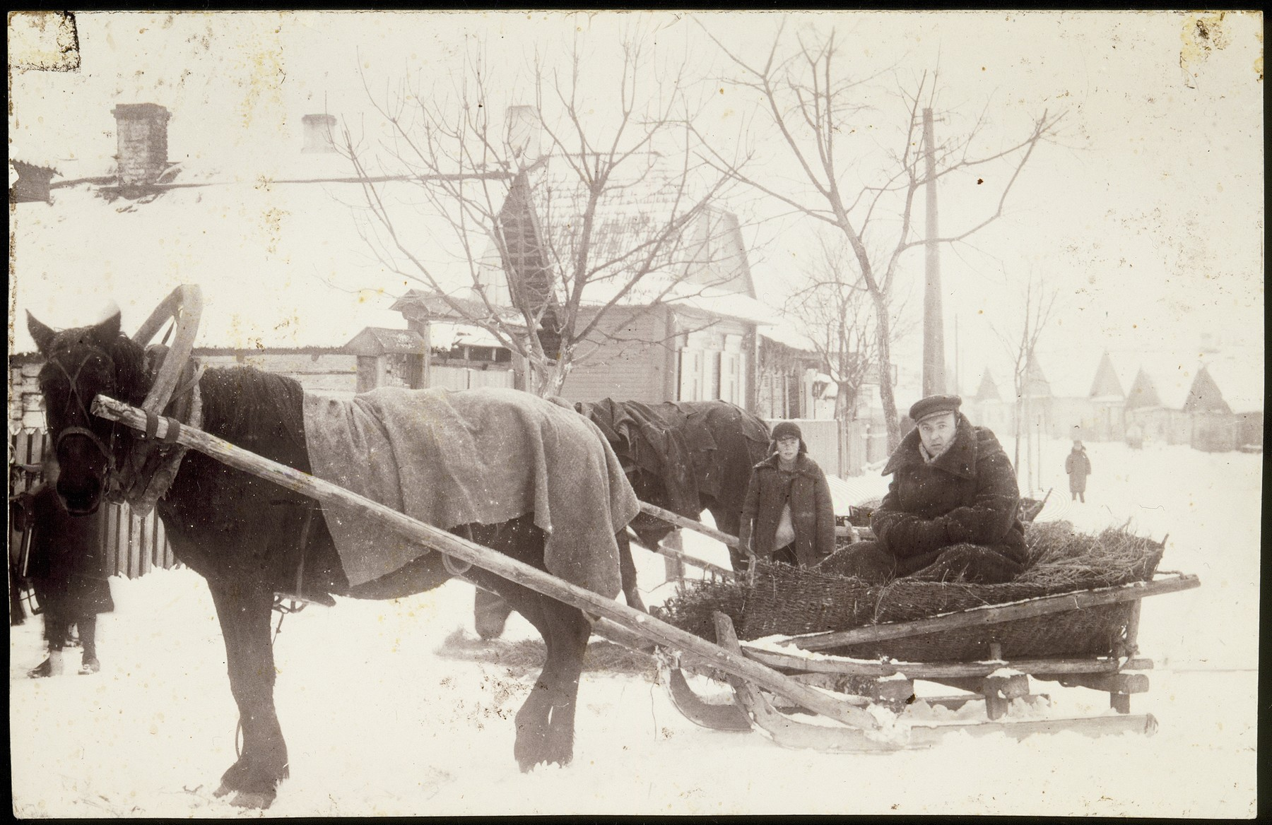 """Dr. Leon Gordon drives to a house call on a horse drawn sleigh through a snowy street in Eisiskes.  On the back of the photo is written """"Sitting in my Packard, 1938 model"""".  Dr. Gordon was killed in Ponar."""