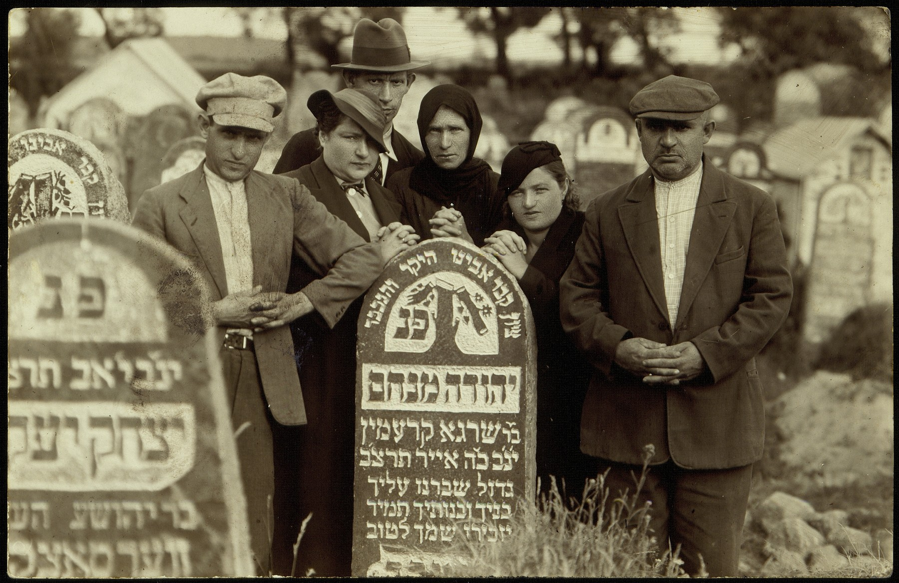 Members of the Kremin family gather by the tombstone of Yehuda Menachem Kremin.  From right to left are Hirsch Faivel Kremin, Rivka Kremin Tatarski, Nehama Kremin Schmidt, Notl Krashunski, Hayya Kremin Krashunski and Hayyim Yitzhak Kremin.  All perished during the Holocaust in Eisiskes, Lida or Grodno.