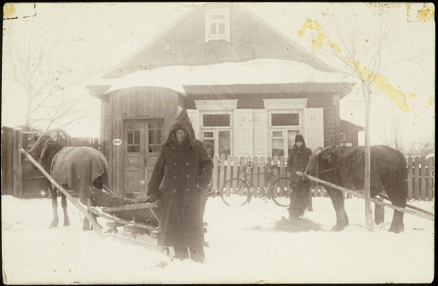 Two men stand by their horses and carts during a snow storm in Eisiskes.