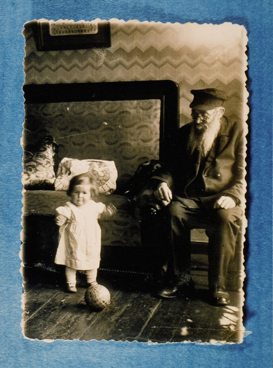 Yosef Ginzberg watches his granddaughter Tamar play with a ball.    Yosef was murdered in Ponar outside of Vilna.  Tamar survived the war in Siberia.