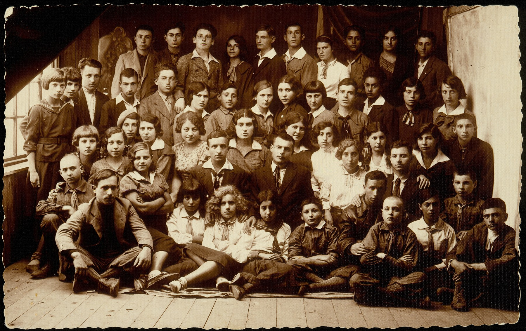 A special meeting of Hashomer Hatzair in Eisiskes attended by counselors from Vilna, including Abba Kovner.    Among those pictured are: top row, from right to left: Boyarski, Krupski, Kaplan, Bichvid, unknown, son of Aronka, Reb Yoshe the coachman's son, unknown;  second rowfrom the top:  Michalowski, Boyarski, Krupski, Bichvid, Cofnas, Portnoy, Borshanski, Levitan (first names are unknown); third row from the top: Herzl, Miriam Lewinson, Lebovitz, Ginunski; fourth row from the top: Garmenishki, Rosenblum, Shalom Kahn, Reuven Paikowski.  Sitting on the floor are Abba Kovner (with his hand on the boy in front of him), Manosh Blacharowicz, and Stoller (the girl in the center with blond curly hair).    Only 11 of those pictured survived the Holocaust, among them Abba Kovner and Reuven Paikowski.