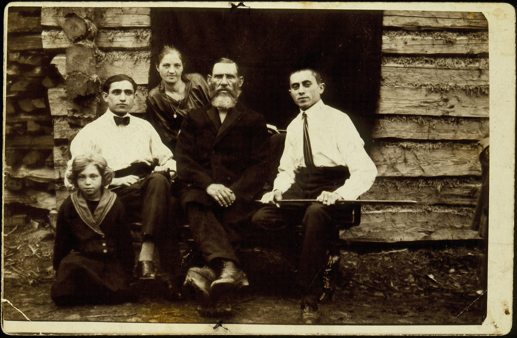 The Kremin family sits at the entrance to a log cabin.   Yude-Mendl Kremin (center), with his son-in-law Hirshl Tatarski (right), daughter Rivka Tatarski, son Hayyim-Itchke, and granddaughter Hayya-Rochke Shmidt.   Yude-Medl had a clubfoot as a result of a severe beating by Lida coachmen during a labor dispute.  Yude-Mendl died a natural death; all the others perished in the September 1941 massacre.