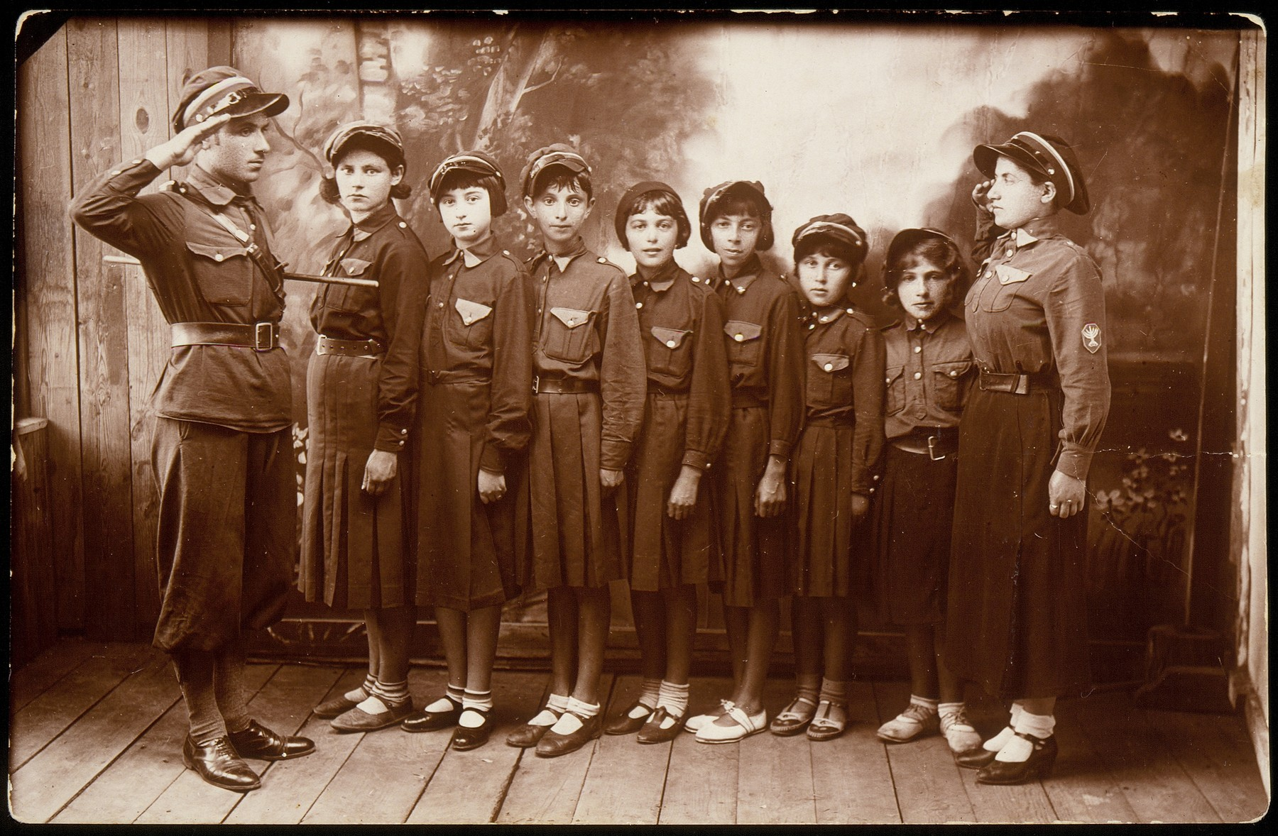 Members of a girls chapter of the Betar revisionist Zionist youth movement in Eisiskes, pose with their leaders.  Pictured from right to left are: Shifra Berczanski, Hanna Sczczuczynski, ? Koppelman, Matke Shlepak, ? Portnoy, unknown, Sarah Tatarski, ? Schwartz and Zvi Hirshke Schwartz.  Shifra Berczanski immigrated to Palestine before the war;  Zvi Hirshke Schwartz survived the war as a partisan; Hannah Sczczuczynski was killed by a member of the Polish Home Army, who had been the caretaker of her Polish school.  The others were killed by the Germans during the September 1941 mass shooting action in Eisiskes.