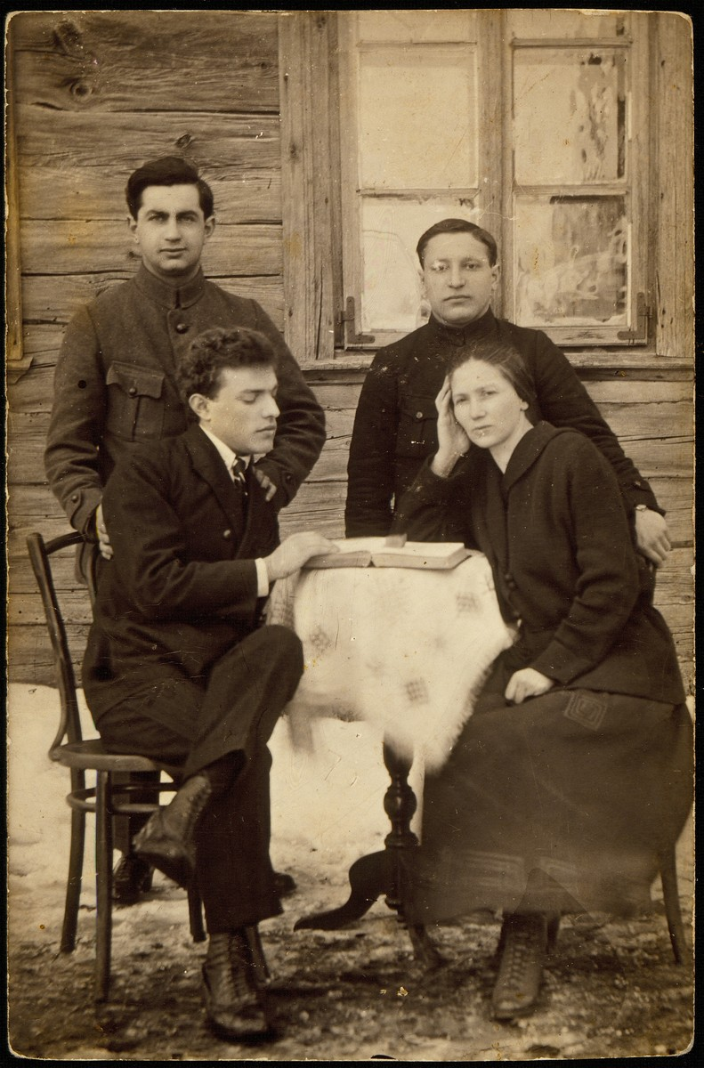 Four young professionals pose around a small outdoor table.  Dr. Adasse, an obstetrician (standing, left) and his nurse F. Sapocrynski (seated, right) were in Eisiskes for a short period.  With them are  Hayyim-Leibl Glombocki (standing, right) and Uri Rozowski, the rabbi's son.  Hayyim-Leibl immigrated to Argentina, Uri to Palestine.