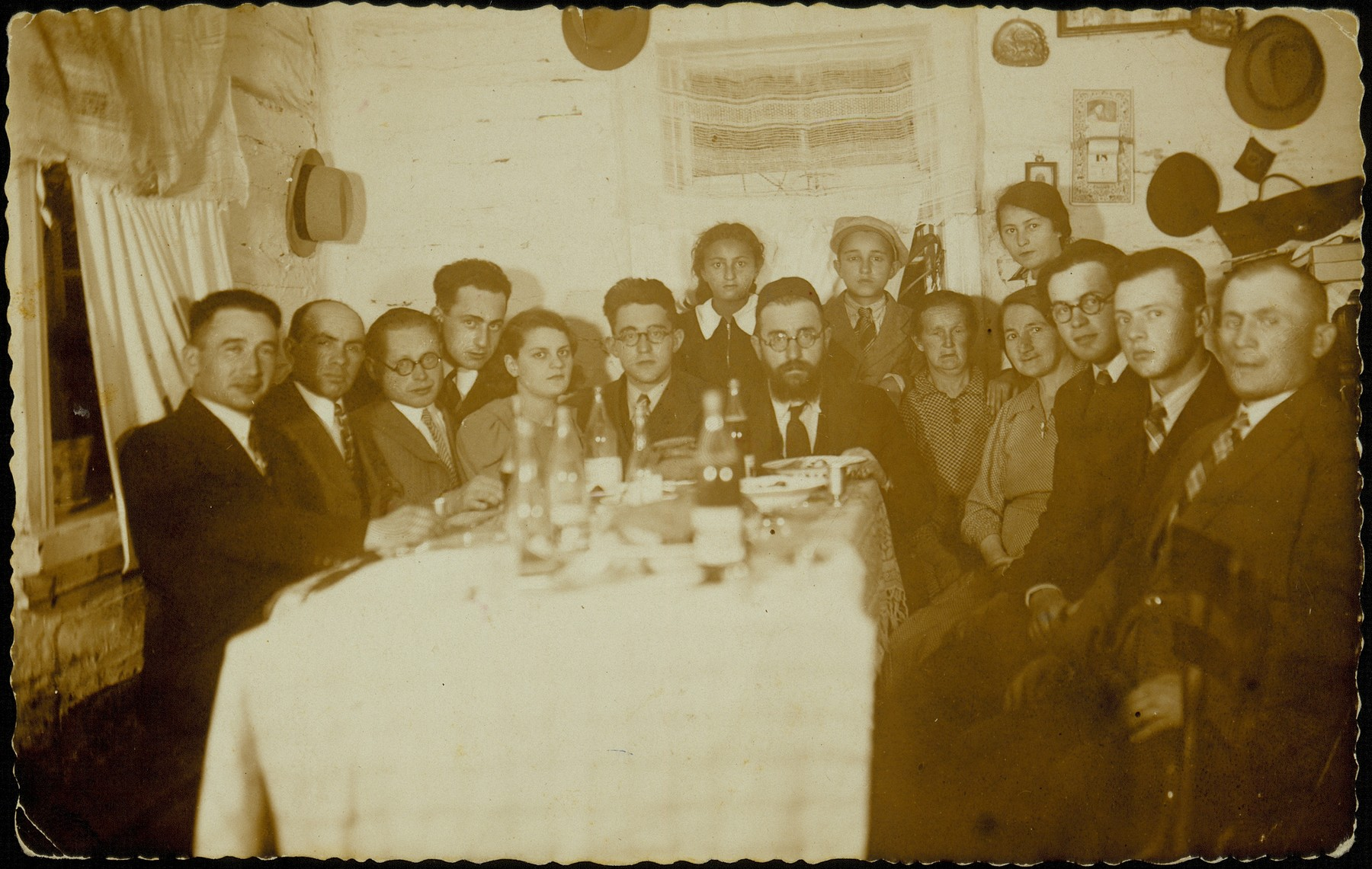 Family party at the home of Reb Israel Yossef and Taibe-Edl (Kabacznik) Hinski on the occasion of the departure of their son, Alexander Zisl Hinski, for Palestine.    Pictured standing in back from right to left are: Golda Braha, Avraham Yaakov and Hayya-Sheine Hinski.  Sitting around the table from right to left are: Gershon Koppelman, Shlomo Dubczanski, Yitzhak Matikanski, Hinda Levin, Taibe-Edl Hinski, Reb Israel Yossef Hinski, Alexander Zisl Hinski, Shmuel (last name unknown), unknown, Ephraim Karnewski, unknown and Mendl Politacki.  Hayya-Sheine Hinski died a natural death during the summer of 1941.  Shlomo Dubczanski and the family of Reb Israel Yossef Hinski (apart from Alexander Zisl) were killed by the Germans during the September 1941 mass shooting action in Eisiskes. Yitzhak Matikanski was killed in Majdanek; Ephraim Karnewski died while hiding in the forest.  The fate of the others is unknown.