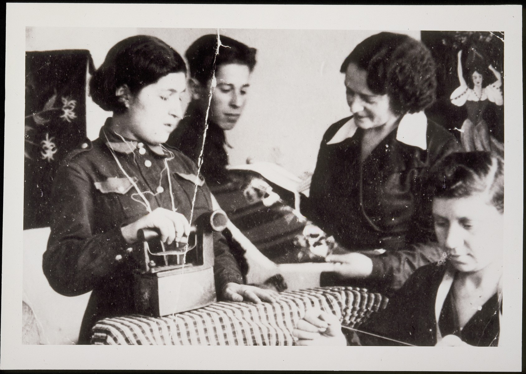 Rochel Szulkin, instructs two young apprentices in her sewing workshop in Eisiskes.  Pictured are Rochel Szulkin (standing on the right) with Hayyim Yoshke Bielicki (second from the left) and Gitta Politacki Ginsberg (wearing the Betar uniform).  Hayyim Yoshke and Gitta survived the war in the Soviet Union; the others were killed in the September 1941 massacre in Eisiskes.