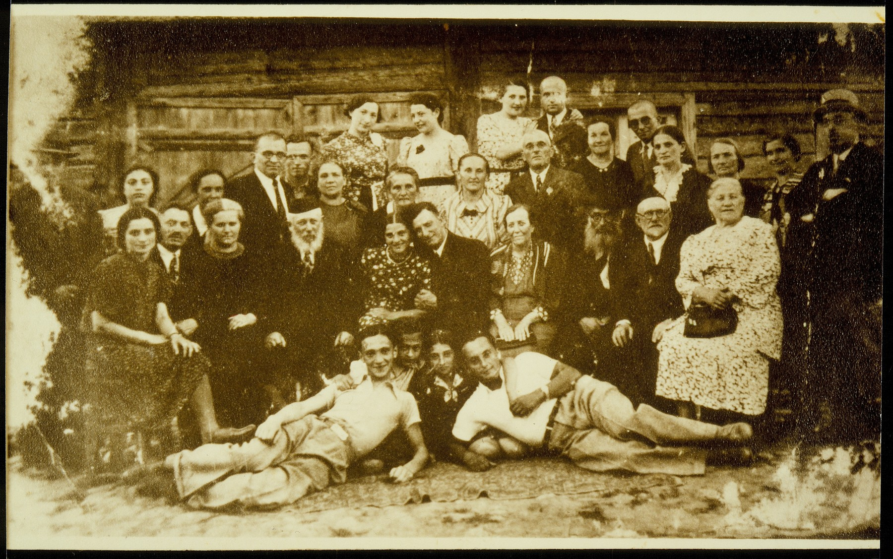 Wedding guests gather for a group portrait in front of the house of Leibke Levin.      Standing at the far right is Moshe Yaakov Botwinik, the principal of the Hebrew School and his wife.  Szeine Blacharowicz is standing in the back at the far left.  Moshe Yaakov Botwinik and his wife were murdered in the Radun ghetto.  Most of the people in the photo were murdered by the Germans in the September 1941 mass killing action.  Szeine Blacharowicz survived the Holocaust in hiding in the forest.