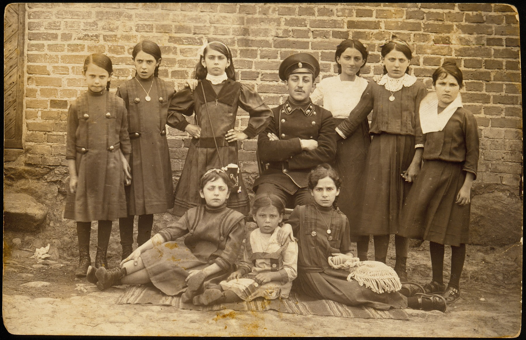 Students in the first girls school in Eisiskes which opened at the turn of the twentieth century.   Among the girls in the photo are the four Glombocki sisters.  Two are standing on the left, one is sitting on the ground, far right.  Next to Ettl Glombocki (Ginsberg) standing second and fourth from right are the Kiuchefski sisters.  First girl to the right is Itka Nochomowicz; third from right is Hinda Sonenson.  Top row (on far right) is Dubraska Peretz .   A number of the Glombockis immigrated to Argentina.  Ettl survived in Russia, Hinda was murdered with her four children in the September 1941 massacre.
