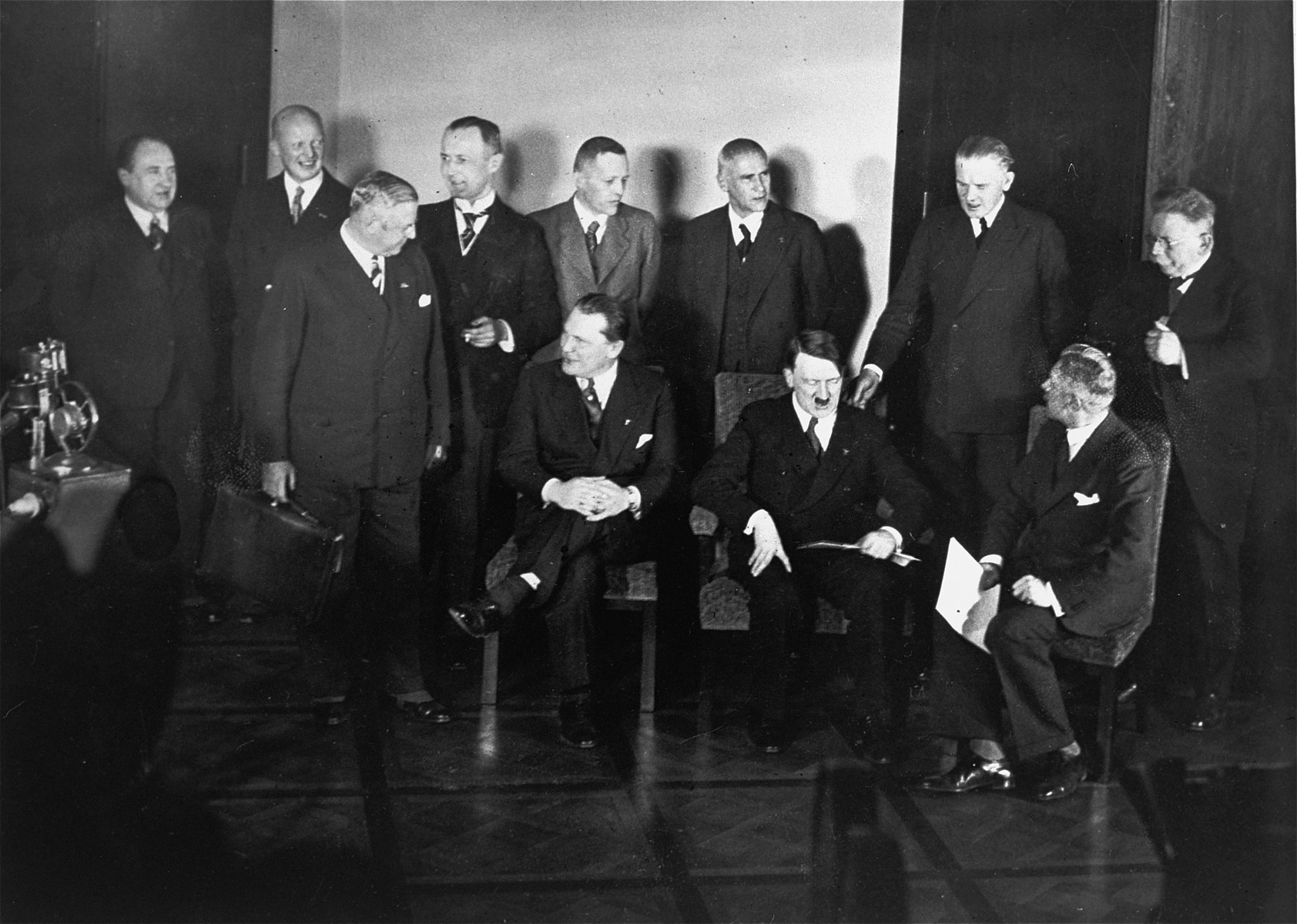 Adolf Hitler poses with members of his first cabinet in the chancellery.  Standing (from left to right): Walther Funk, Hans Heinrich Lammers, Walther Darre, unidentified, unidenrified, Wilhelm Frick, unidentified, unidentified.  Sitting (left to right): Hermann Goering, Adolf Hitler, and Fritz von Papen.
