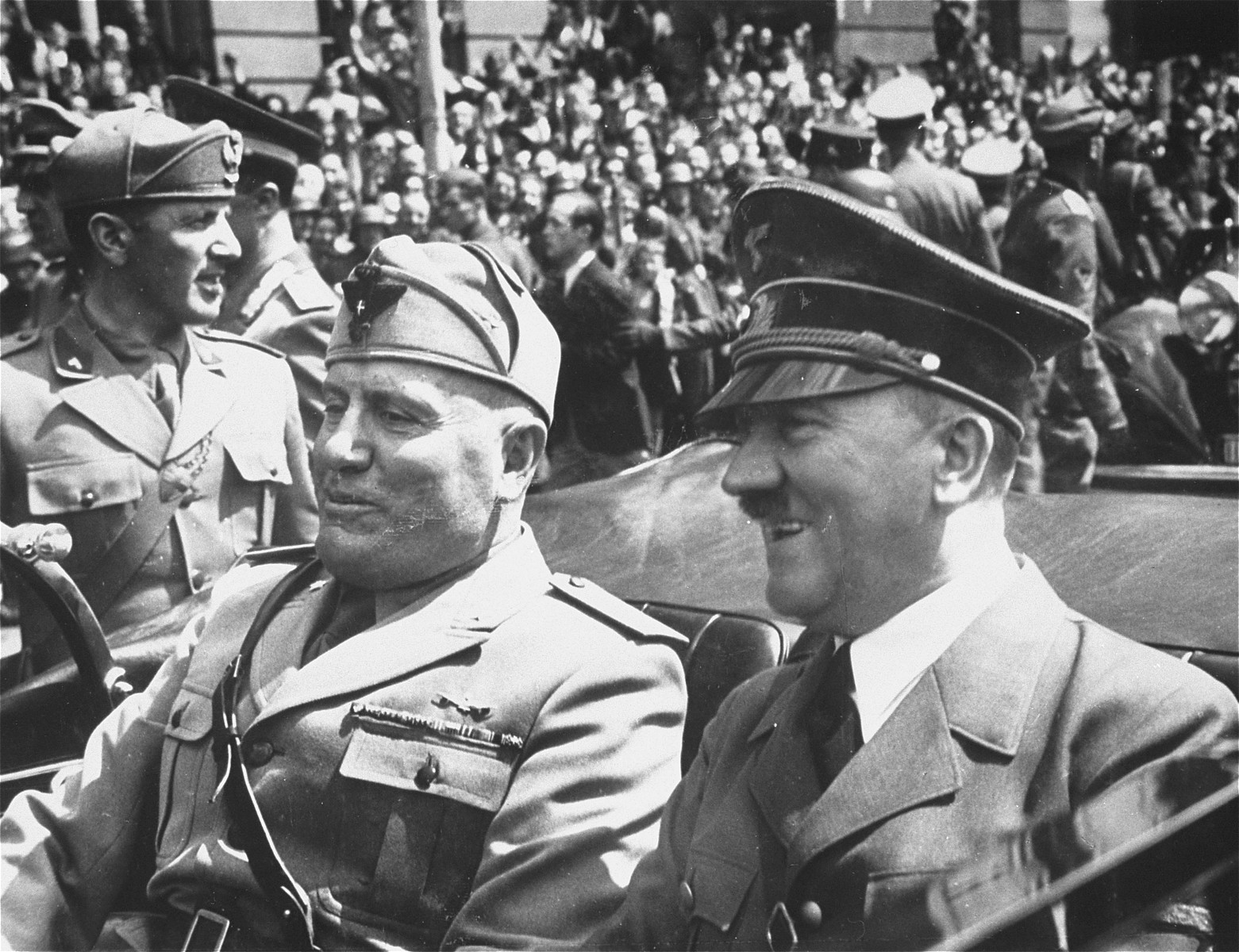Adolf Hitler and Benito Mussolini ride in an open automobile through the streets of Munich during the Italian dictator's visit to Germany.
