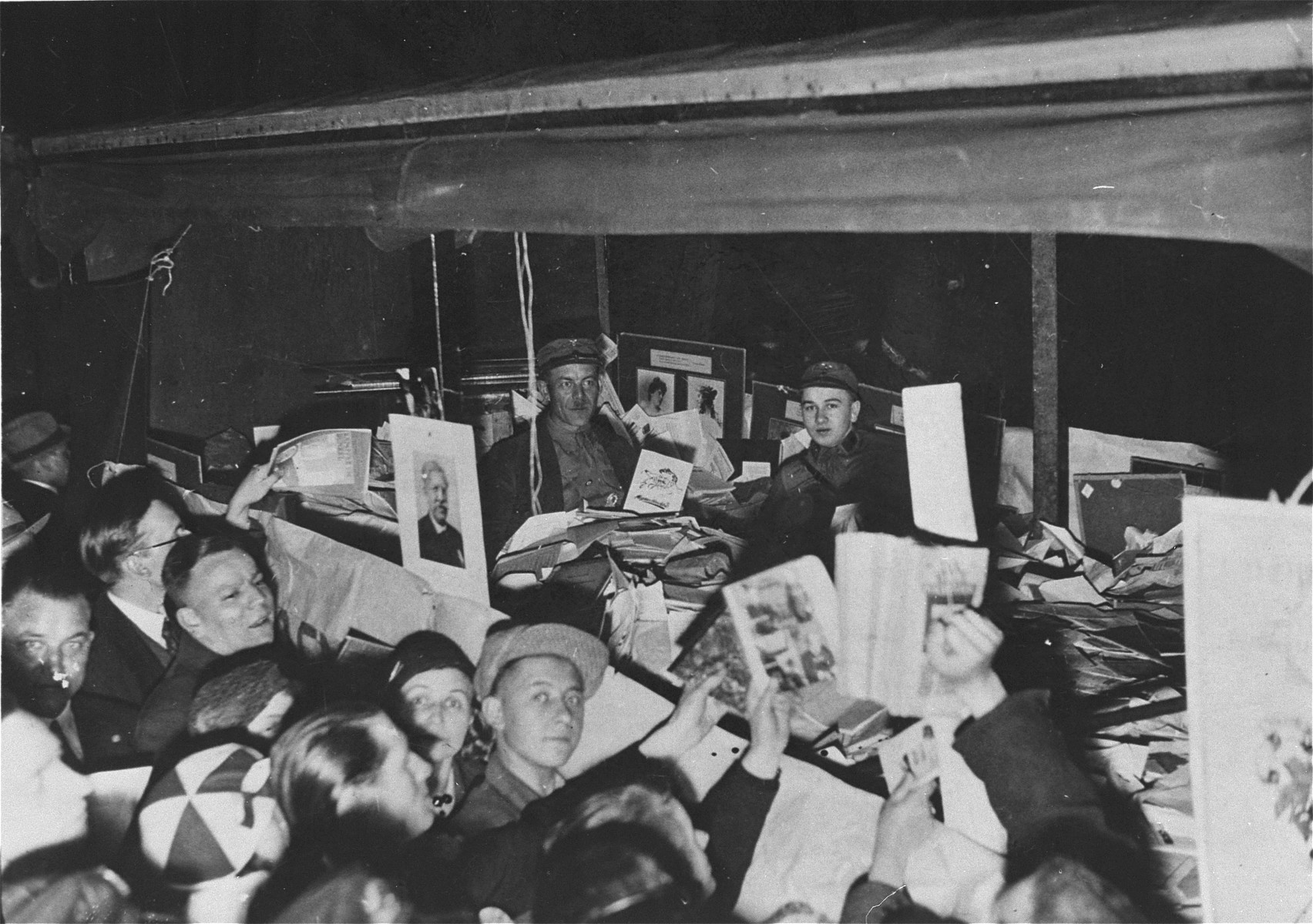 "Germans crowd around a truck filled with ""un-German"" books, confiscated from the library of the Institute for Sexual Science,  for burning by the Nazis.    In the background there is a panel of the ""Zwischenstufenwand"" (Wall of Sexual Intermediates), which hung at a prominent place in the Institute. Photo from the plundering of the Institute for Sexual Science 81919-1933) on May 6, 1933. (Institut für interdisziplinäre Sexualforschung, Hamburg)"