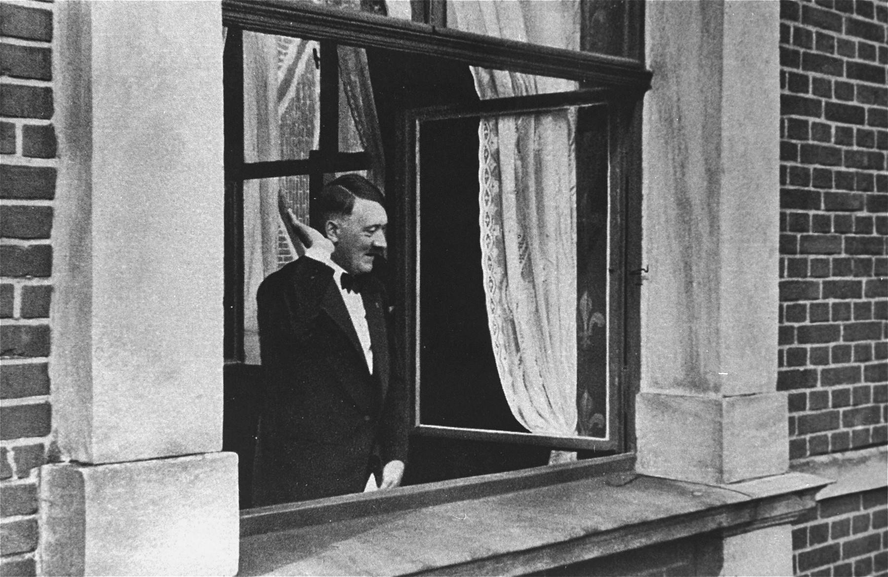 Adolf Hitler salutes a crowd from the windows of the Chancellory.  This photograph, perhaps a reenactment of his assumption of power on January 30, 1933, was reprinted as a propaganda postcard.