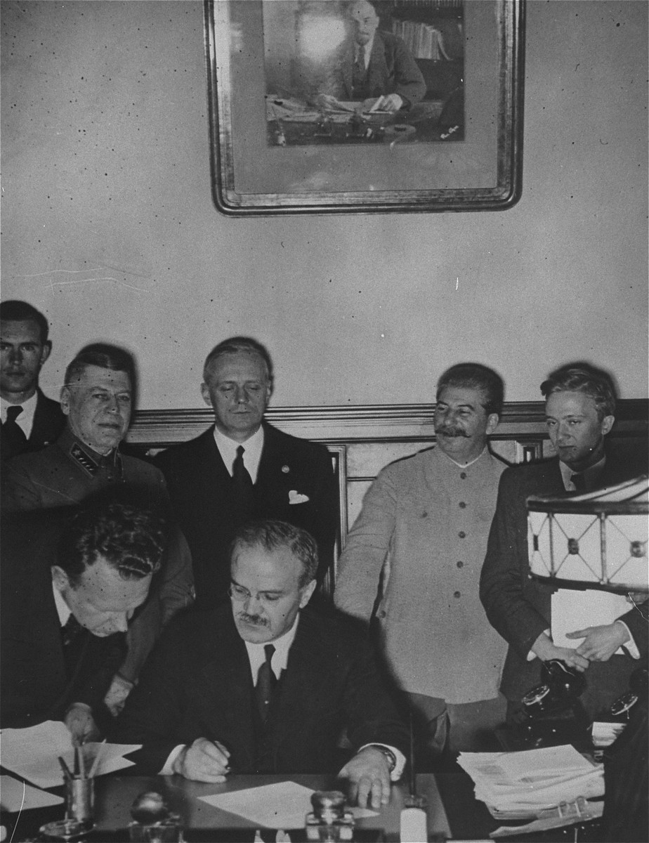 Soviet foreign minister Vyacheslav Molotov signs the Nazi-Soviet Non-Aggression Pact.  Among those pictured are Marshal Yevgeny Shaposhnikov (standing second from the left), Joachim von Ribbentrop (standing behind Molotov), and Joseph Stalin (standing second from the right).