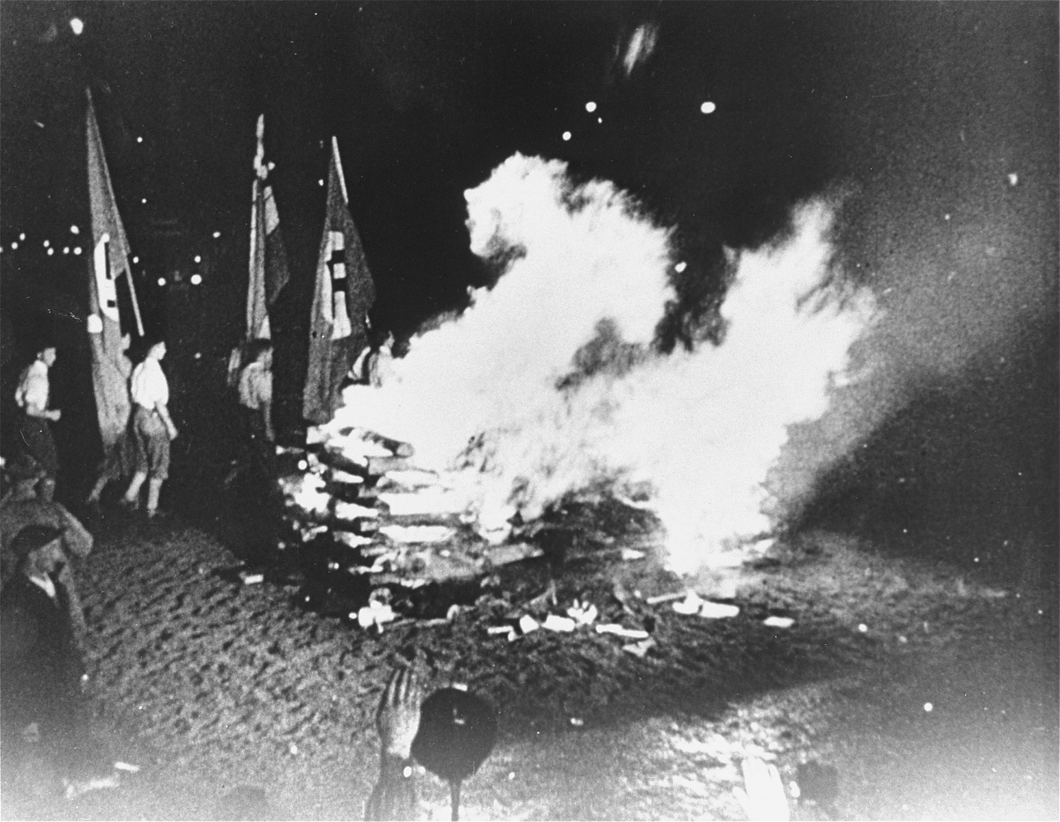 """Students carrying Nazi flags march around the bonfire of """"un-German"""" books on the Opernplatz in Berlin.   Still from a motion picture."""