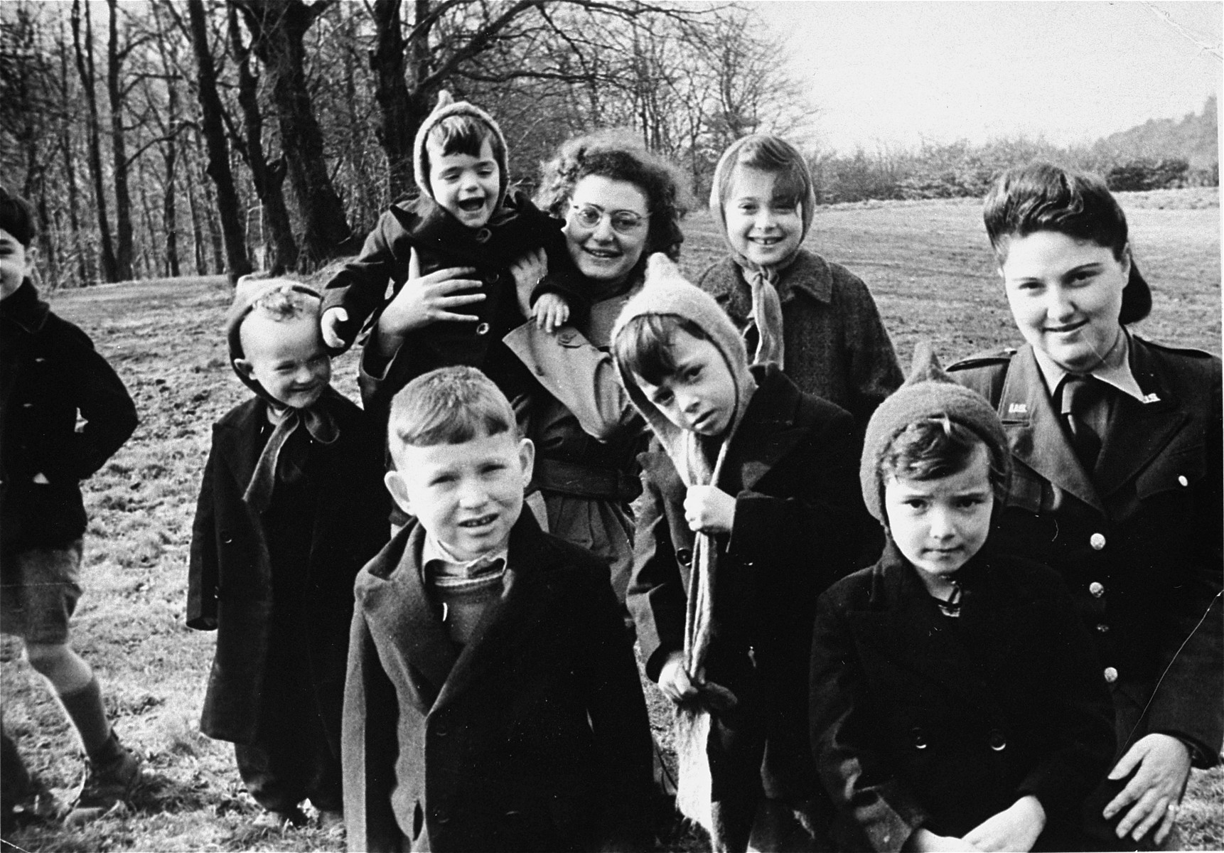 Orphans from Warburg children's home pose outside with JDC relief workers.     Pictured at the far right is Sally Bendremer; Hilde Jacobstahl holds the child in the center. The boy walking out of the picture on the far left is Peter Salomon (Peter Ruben Lewkowitz) now known as Yiphtach Ronen.