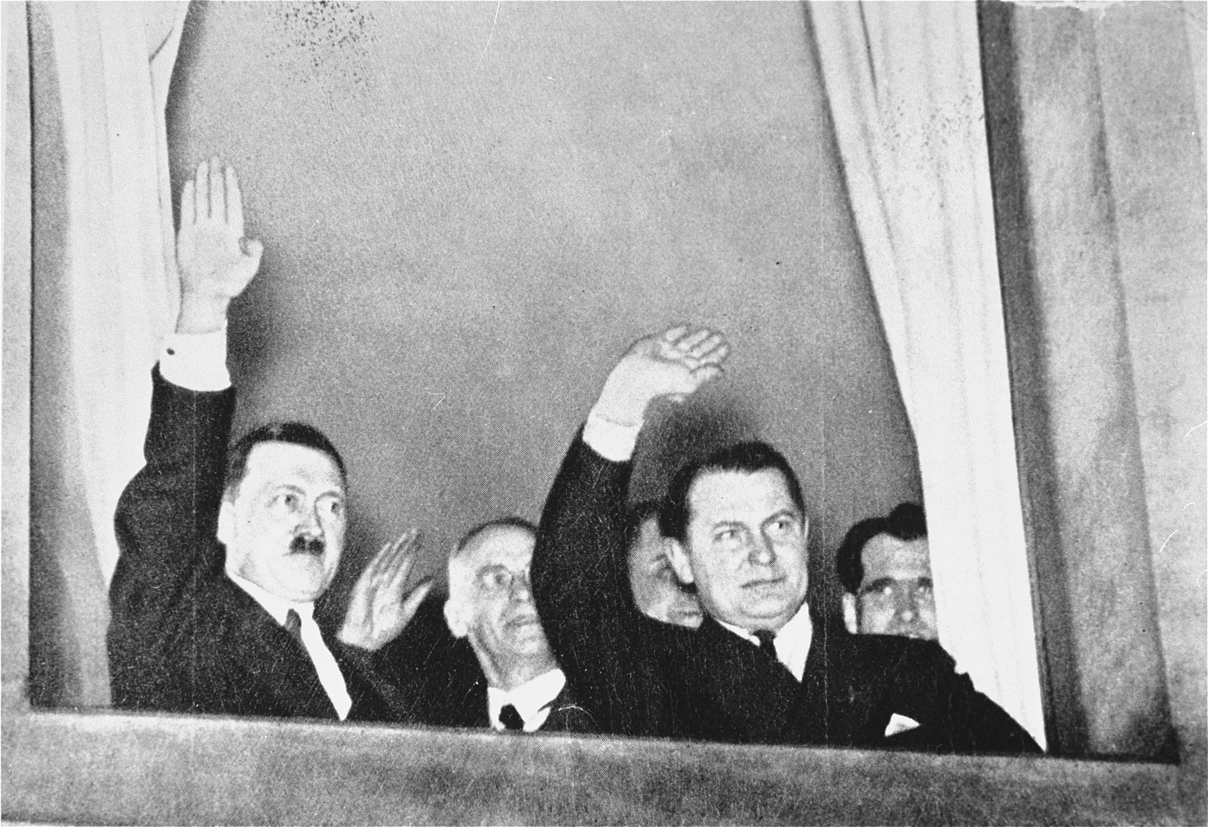 Adolf Hitler, Wilhelm Frick, Hermann Goering and Rudolf Hess greet participants in an SA and Stahlhelm torchlight parade in honor of Hitler's appointment as Chancellor as it passes by the chancellery.