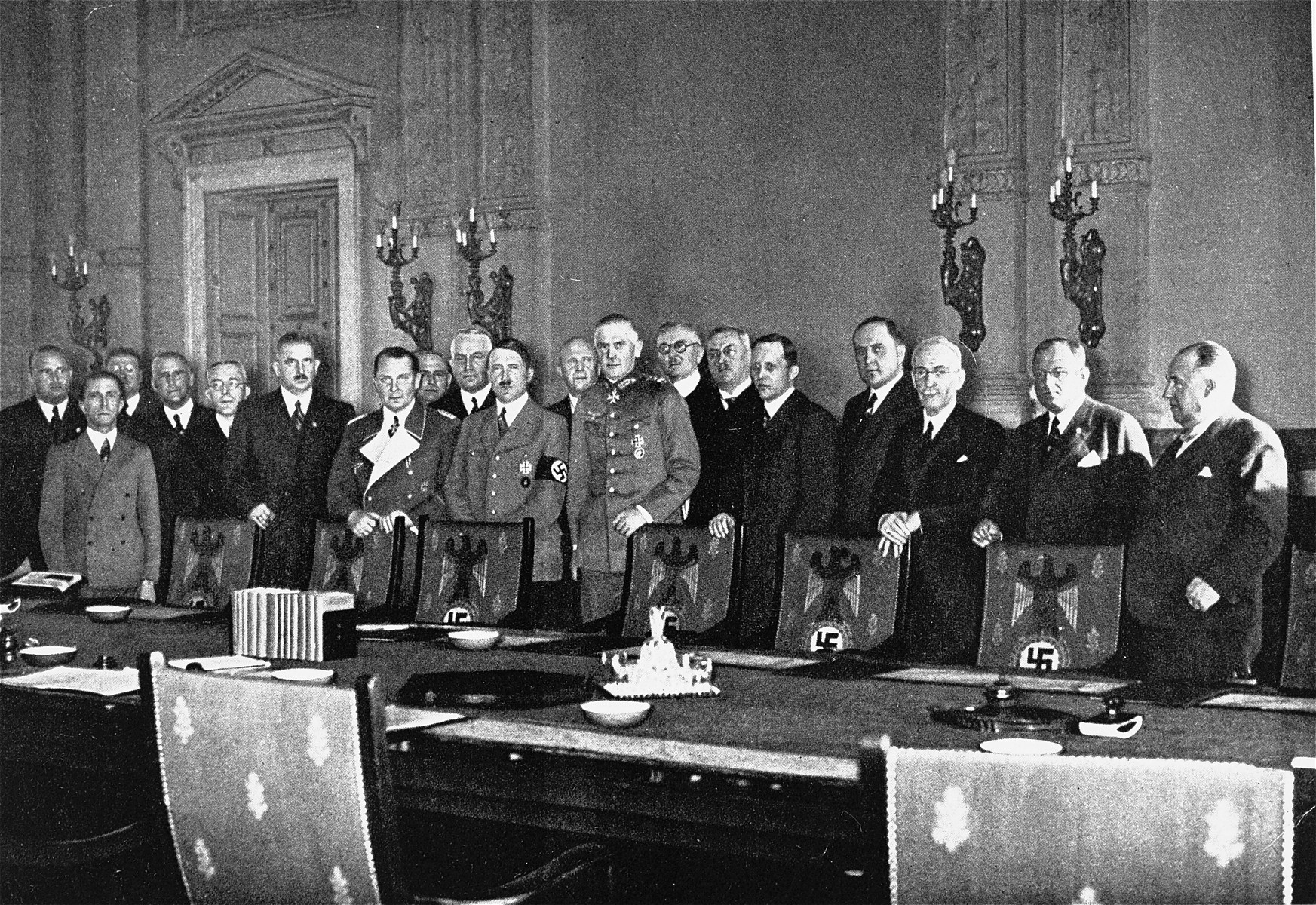 Adolf Hitler poses with members of his first cabinet in a conference room of the chancellery on the occasion of the announcement of new national defense legislation.