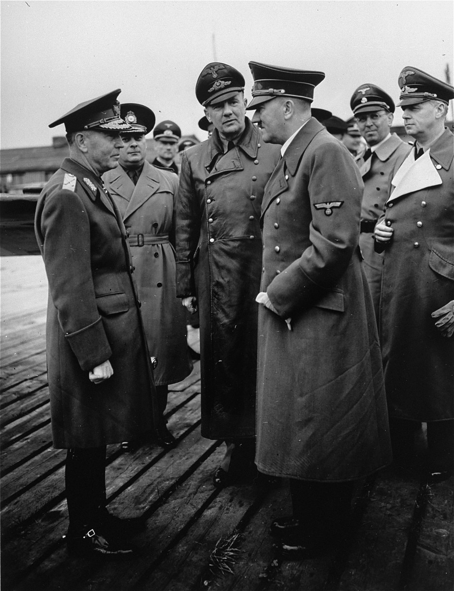 Romanian dictator, Marshal Ion Antonescu (left), converses with Adolf Hitler during an official visit to Germany, as Nazi officials look on.  Pictured in the center is Hitler's interpreter, Paul Schmidt.  Second from the right is Julius Schaub and at the far right, Joachim von Ribbentrop.