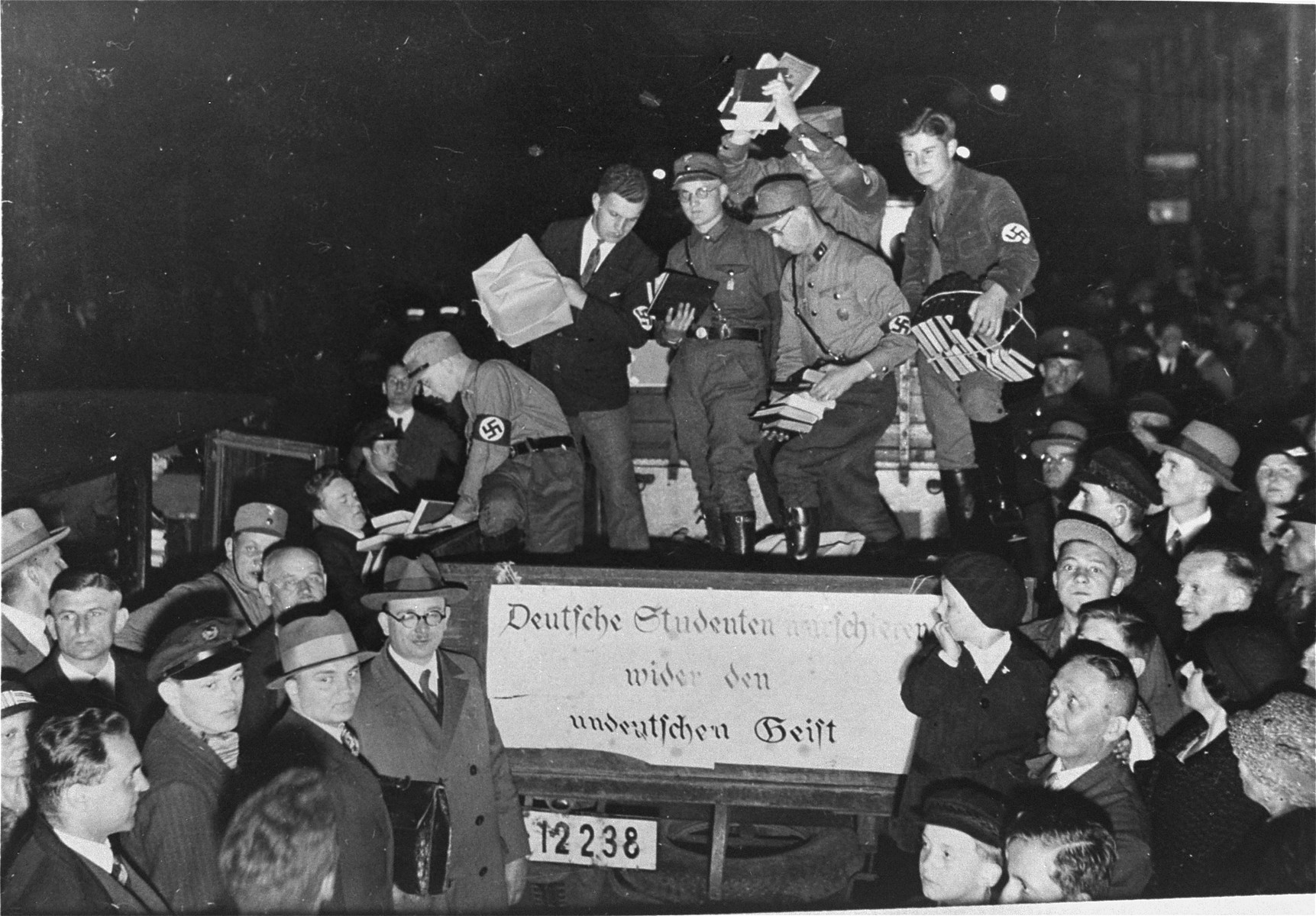 "Nazi students unload confiscated materials for the public book burning that is to take place on the Opernplatz in Berlin.  The banner on the back of the truck reads: ""German students march against the un-German spirit."""