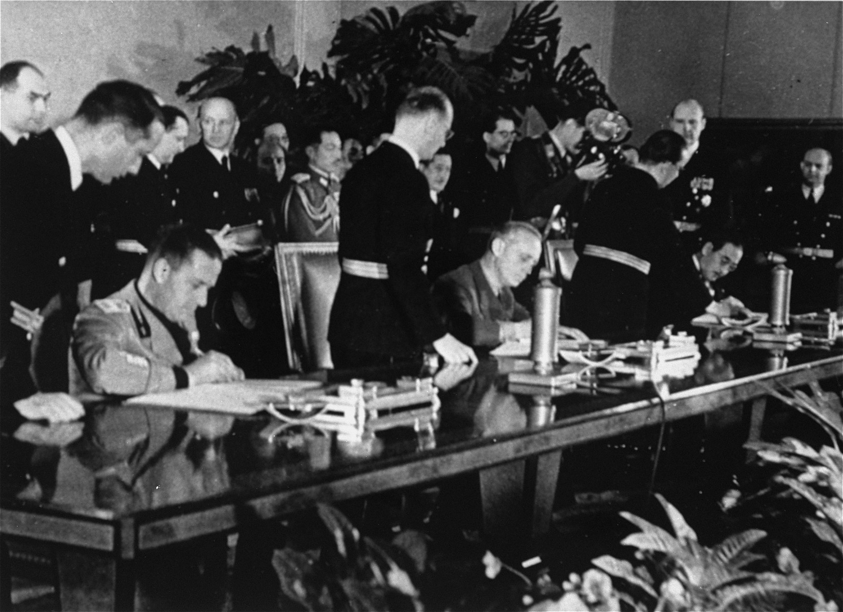 Representatives of the governments of Italy, Germany, and Japan sign the Three Power Pact, establishing the Rome-Berlin-Tokyo Axis.  Seated left to right are: Galeazzo Ciano (Italy), Joachim von Ribbentrop (Germany), and the Japanese ambassador, Kurusu.