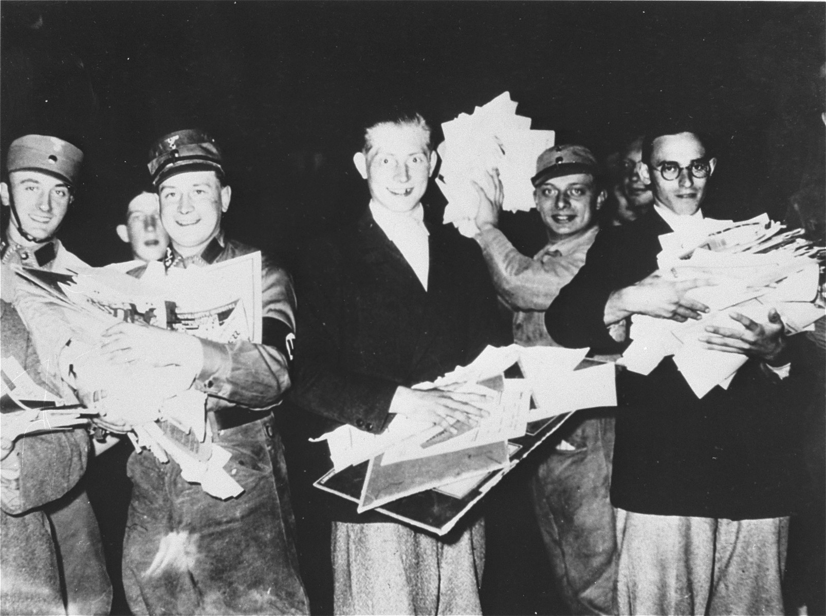 """Students and SA members carry piles of """"un-German"""" literature to throw into the bonfire on the Berlin Opernplatz."""