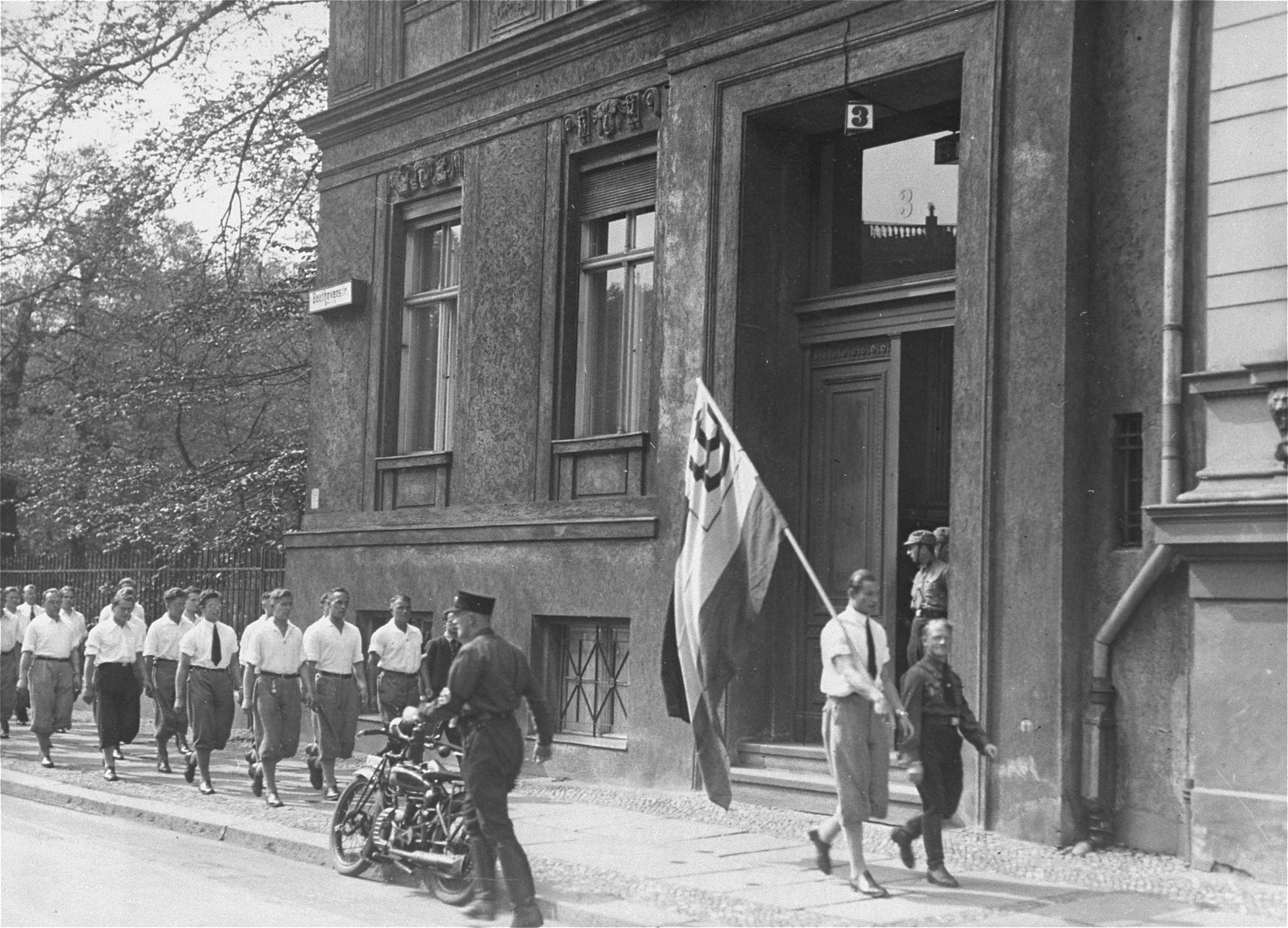 German students parade in front of the Institute for Sexual Research prior to their raid on the building.  The students occupied and pillaged the Institute, then confiscated the Institute's books and periodicals for burning.  The Institute for Sexual Research was established by Dr. Magnus Hirschfeld, a German Jew, as a center for research into sexology.  Members of the institute also provided counseling for homosexuals and transsexuals and fought for the expansion of their political and social rights.