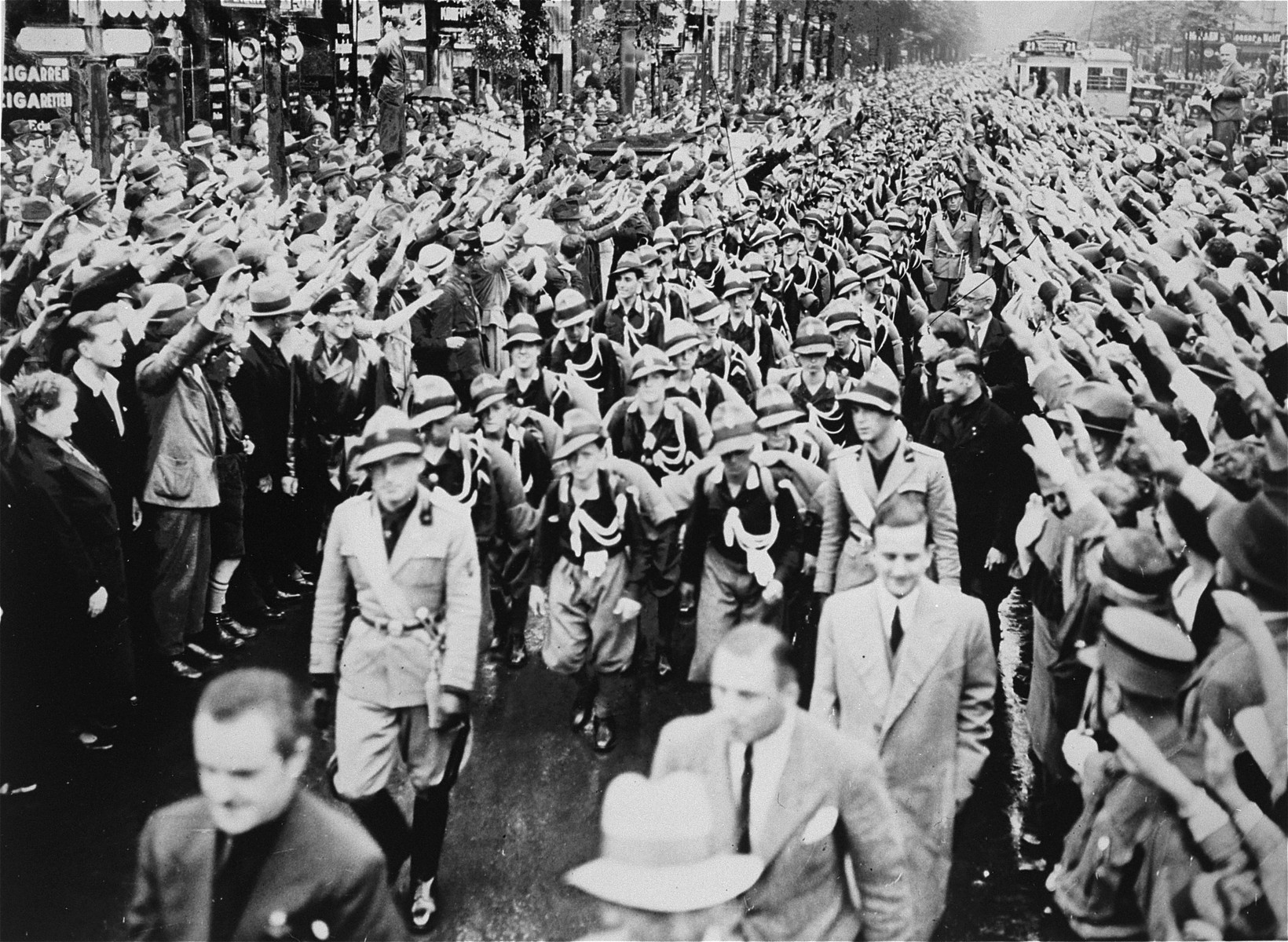 German civilians enthusiastically salute 440 Italian youth as they march through the streets of Berlin while on a state visit to Germany.