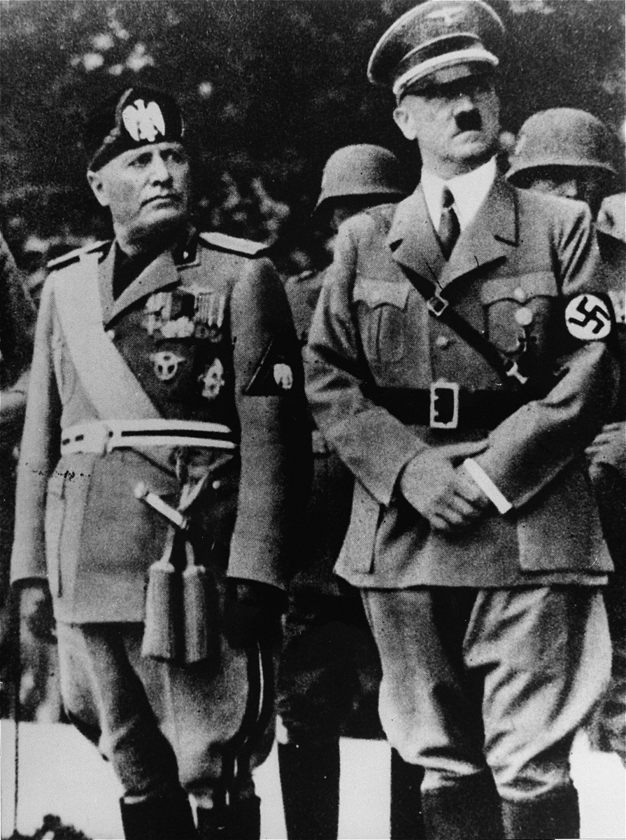 Benito Mussolini and Adolf Hitler stand together on an reviewing stand during a official visit to occupied Yugoslavia.