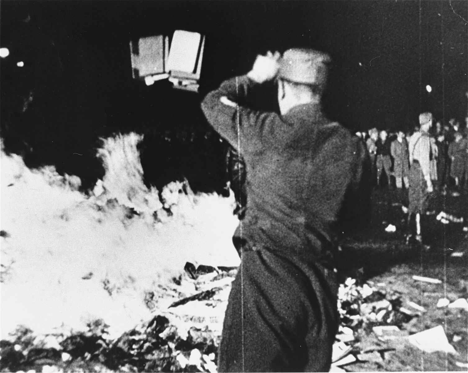 "A member of the SA throws confiscated books into the bonfire during the public burning of ""un-German"" books on the Opernplatz in Berlin.   Still from a motion picture."