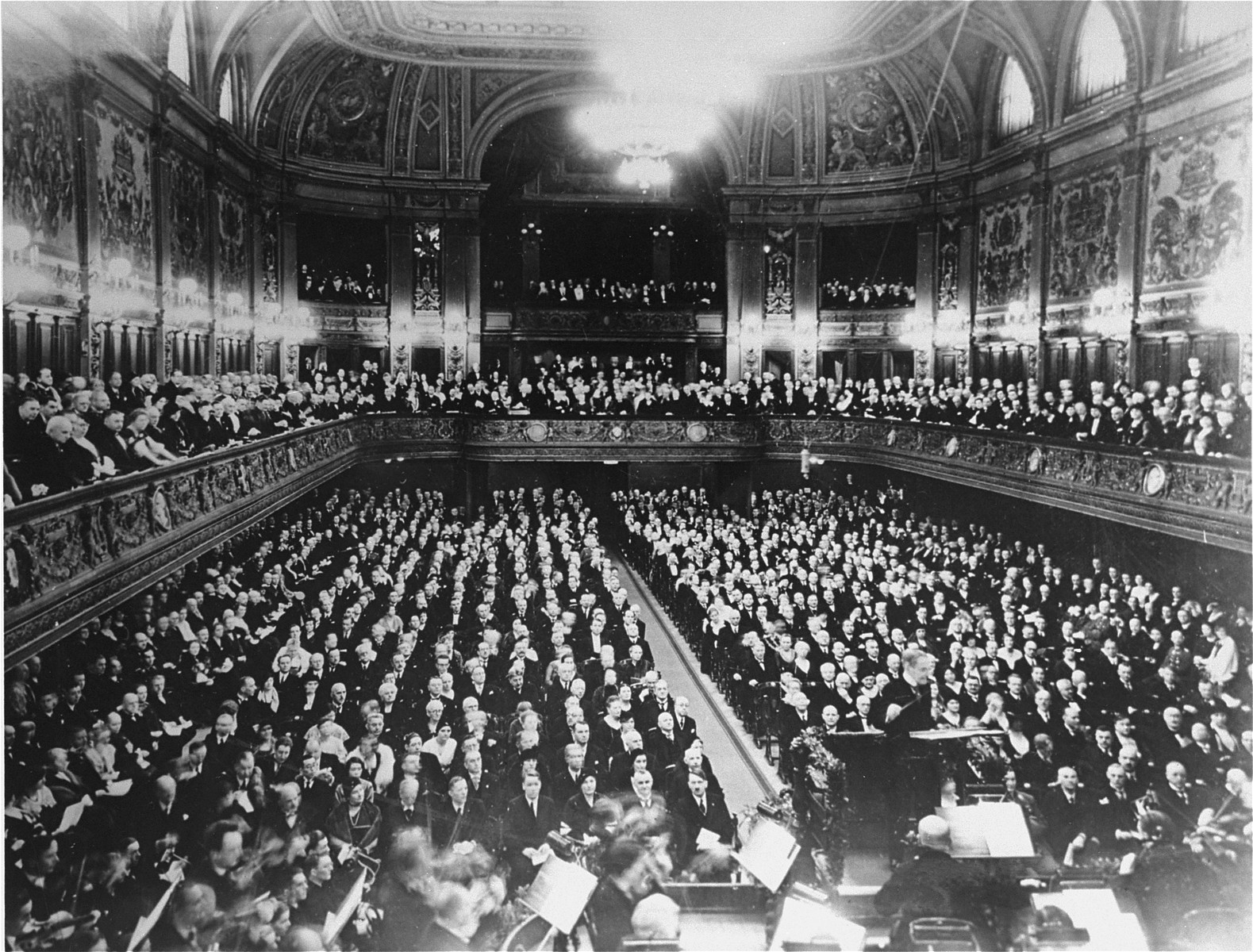 View of the concert audience during a performance of Wagner by the Leipzig orchestra, conducted by Dr. Carl Muck.  Pictured in the front row of the audience is Adolf Hitler (on the aisle).  Sitting next to him from right to left are Dr. Gordeler (mayor of Leipzig), Winnifred Wagner (daughter-in-law of composer Richard Wagner), her son Wieland Wagner, Reichsminister Lutz Schwerin von Krosigk, President of the Reich Supreme Court Erwin Bumke, and Mrs. Bumke. On the other side of the aisle in the front row, from left to right are Reichsminister Hermann Goering (partially obscured by podium), and Reichsminister of Interior Wilhelm Frick.